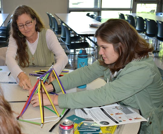 "English as a New Language teachers Mary Ann Daugherty (of Vestal Hills Elementary) and Hilary Loyd (of African Road Elementary) play The Brain Architecture Game after attending a presentation on ""Nature and Nurture: Adverse Childhood Experiences, Brain Architecture and Resiliency."" In the game,  they worked together to build a brain from pipe steams and plastic tubing."