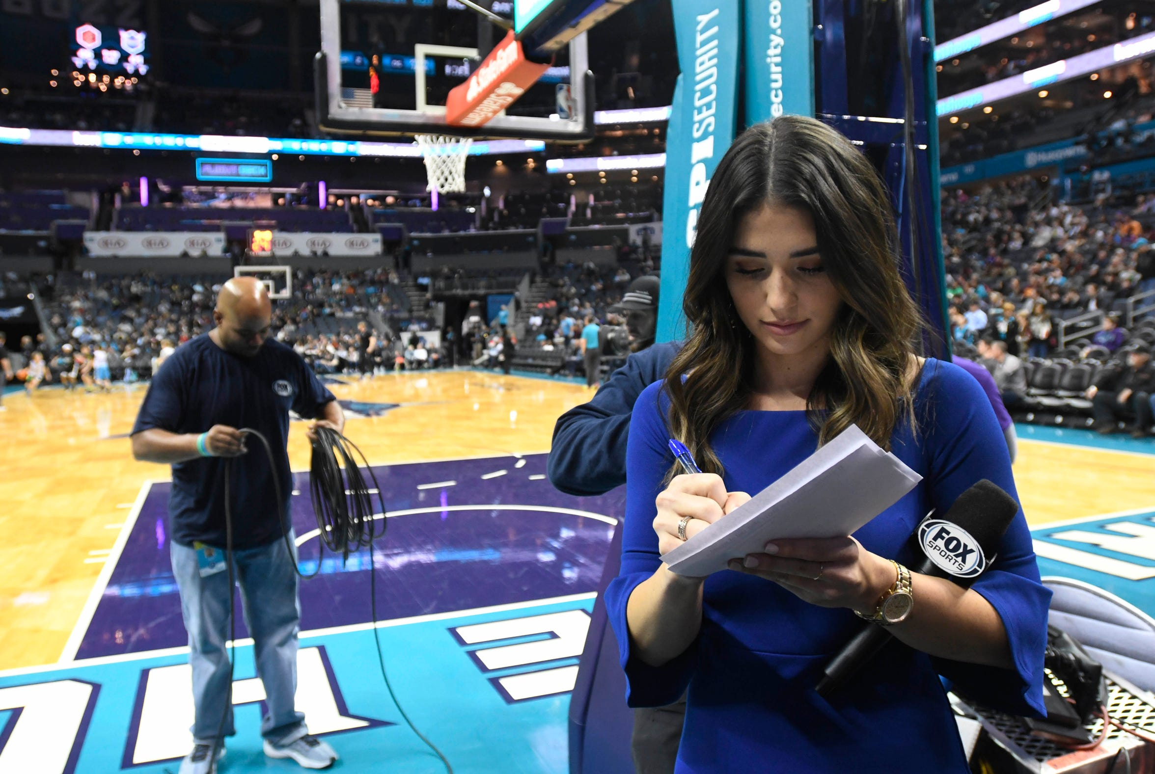 In this Dec. 19, 2018 photo, Ashley ShahAhmadi takes notes along the baseline during halftime of the Charlotte Hornets game against the Cleveland Cavaliers at the Spectrum Center in Charlotte, N.C.
