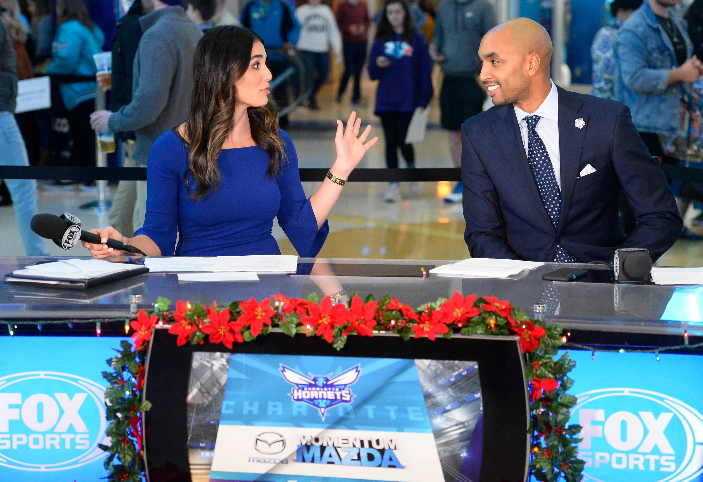 In this Wednesday, Dec. 19, 2018 photo, Ashley ShahAhmadi jokes with former Charlotte Hornet Gerald Henderson prior to the Charlotte Hornets game against the Cleveland Cavaliers at the Spectrum Center in Charlottes, N.C.