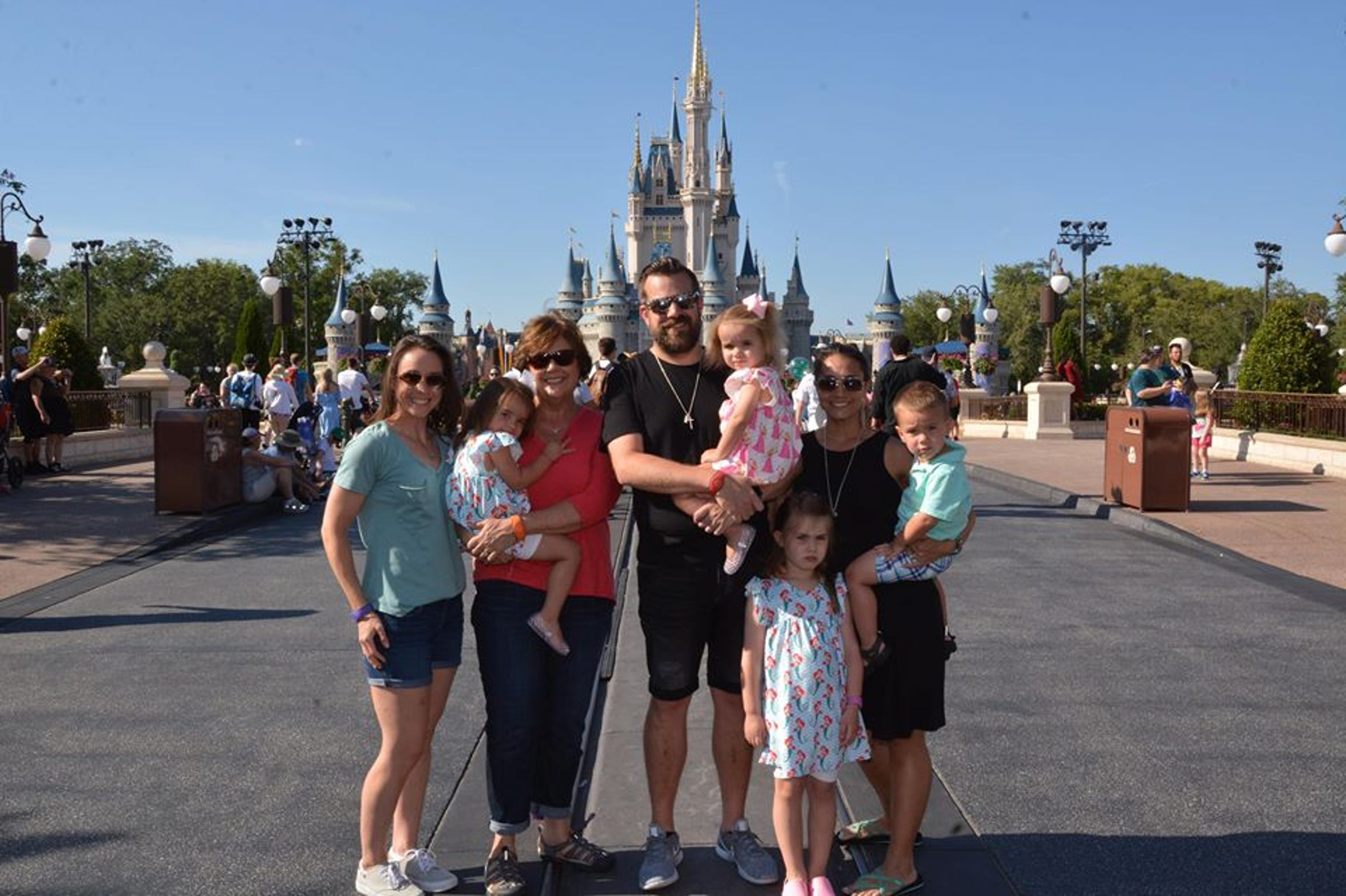Jenna McCue, left, stands with her mother, Gloria Petrowski, and brother and sister-in-law, Justin and Kara Petrowski at Walt Disney World in Orlando, Florida. McCue was highly invested in her nieces and nephews (front). Justin said she loved taking them on rides at the park.