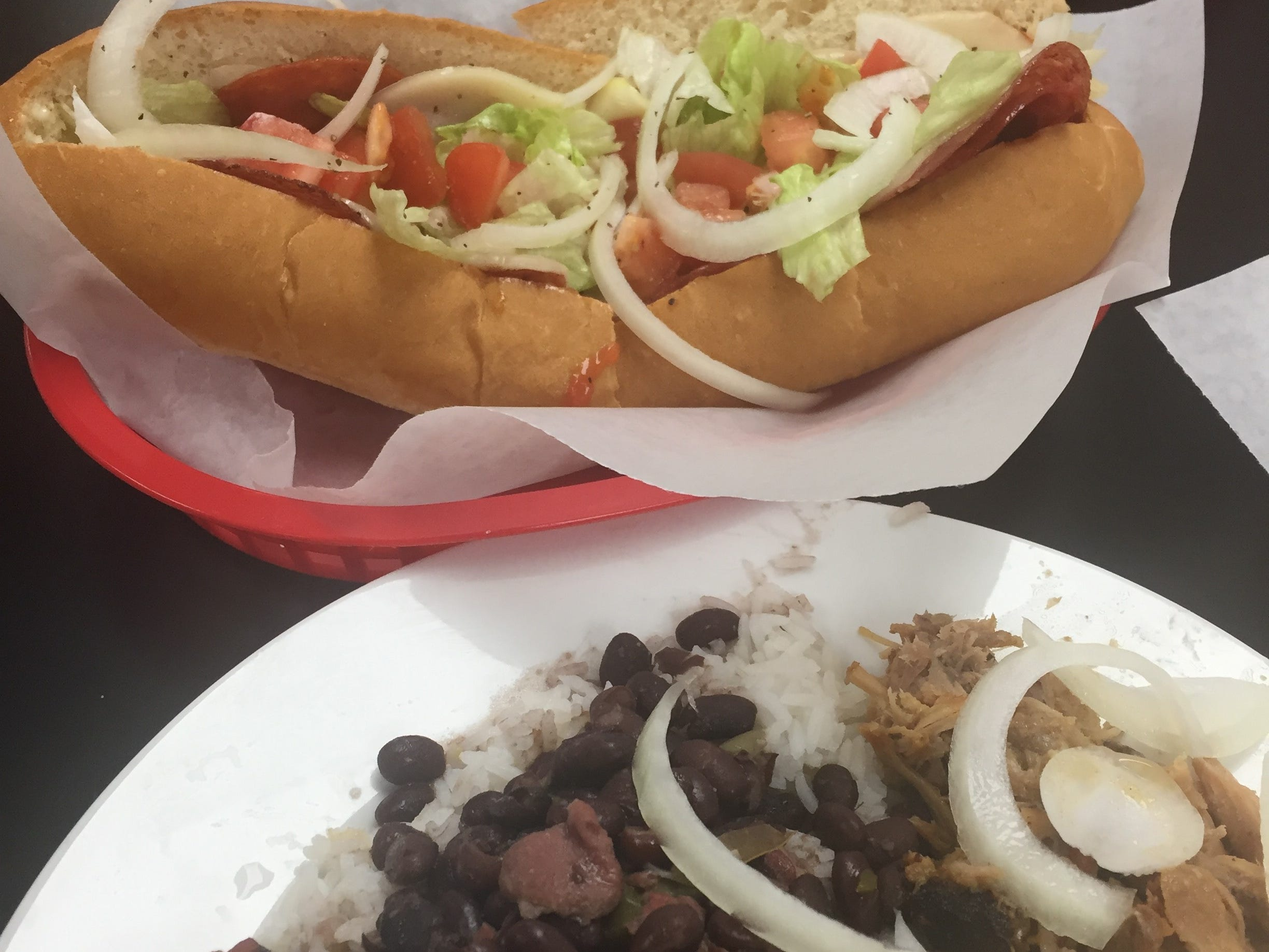 Two options at Halls Deli Cuban Café are a platter made with marinated pork and served with white rice, a choice of beans and a choice of plantains, front, and a grilled Italian sub.