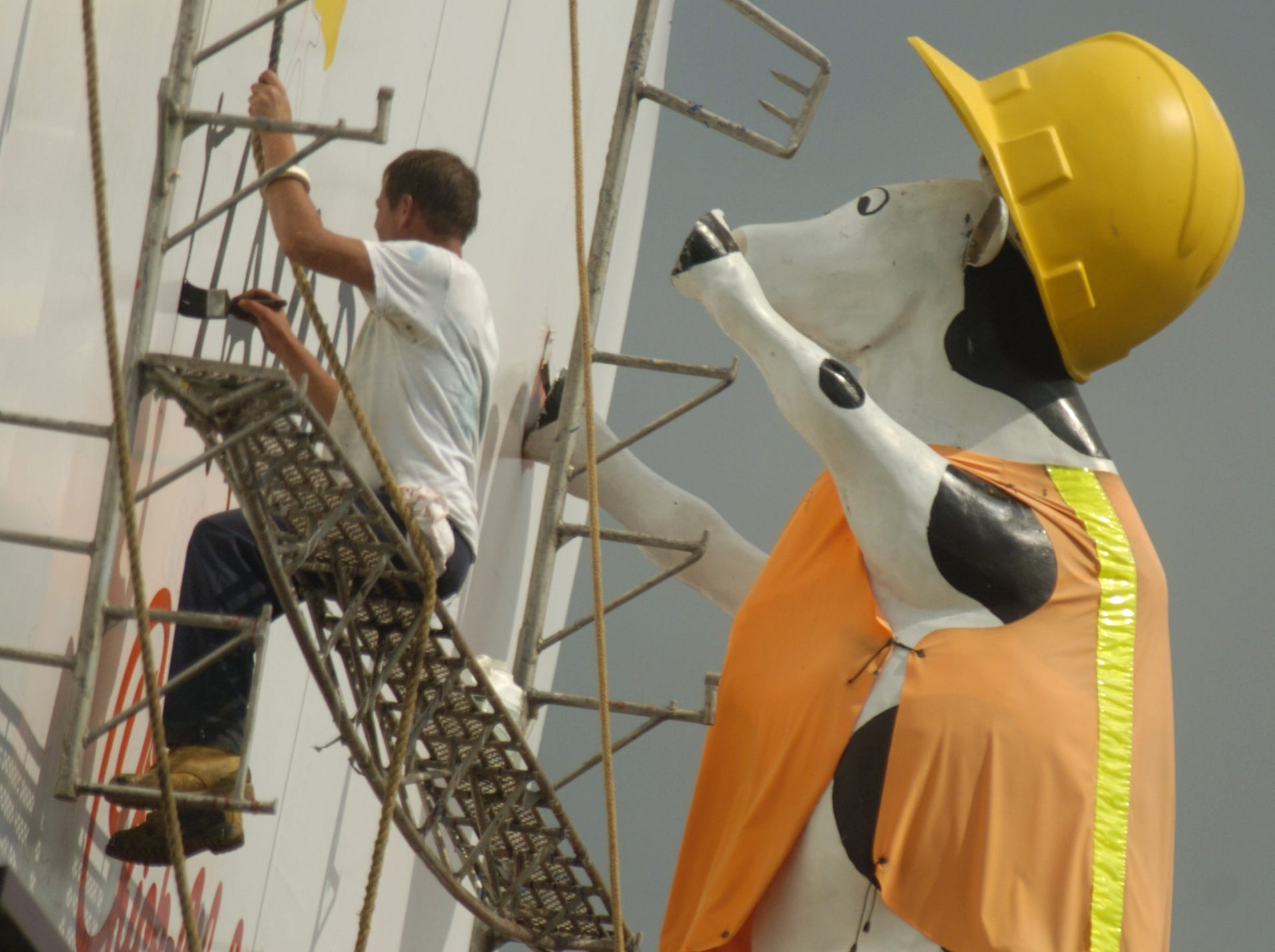 Dale Fisher of D.J. Sign Company, who does sub-contracting work for Douglas Outdoor Advertising of Knoxville, paints a new Chick-Fil-A sign on a billboard as he appears to be imitating a giant cow dressed in a construction outfit which is part of the billboard. Fisher was working with Jake Crawford, not pictured, high above Interstate 40 near the Cedar Bluff Exit Monday afternoon. Crawford says that he and Fisher paint two different Chick-Fil-A billboards along the Interstate for Douglas about once a year. 6/19/2004