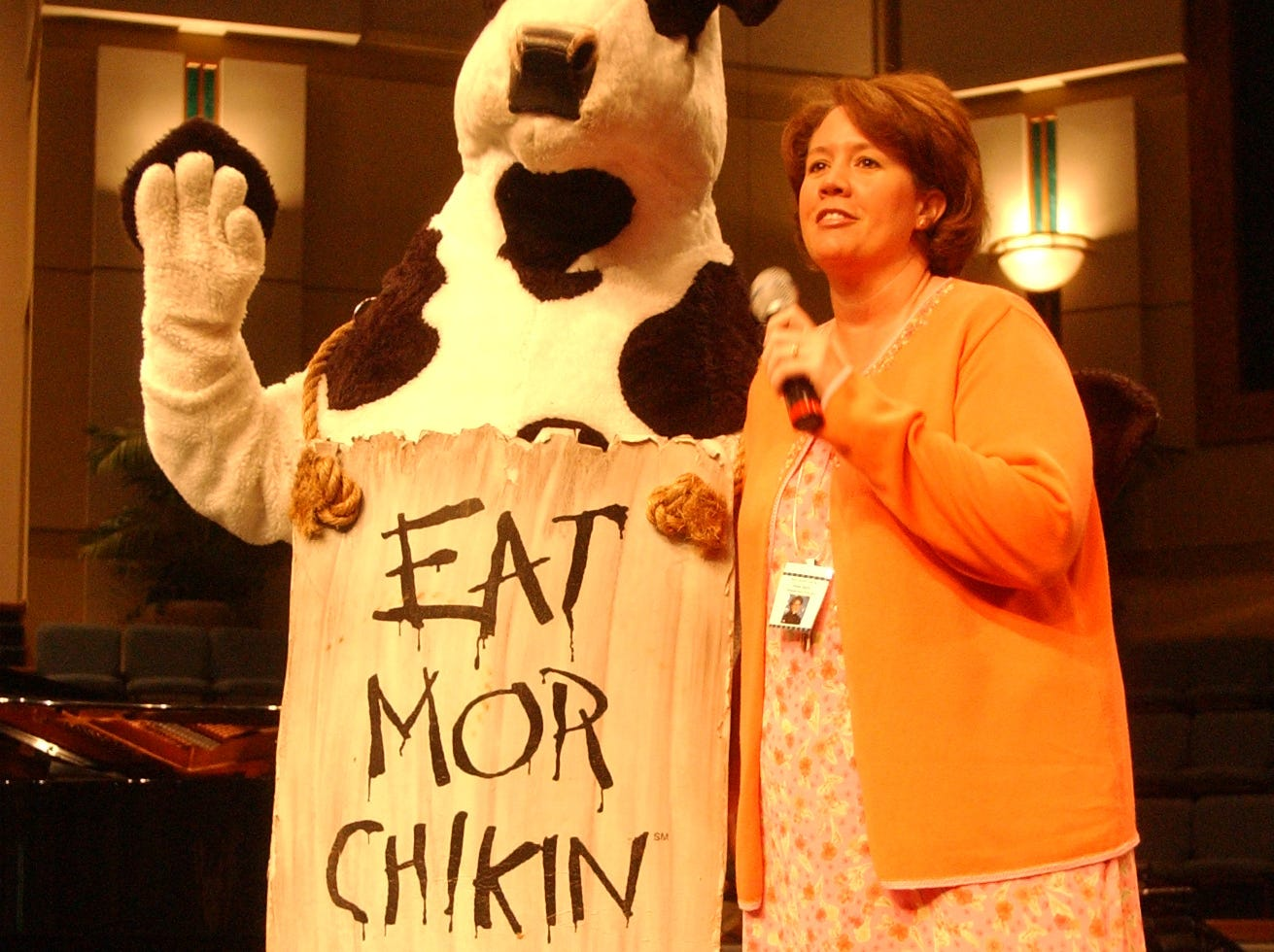 The Chick-fli-A cow is introduced by Grace Baptist Church School elementry school principal Susan Barnes duriing a Chapel Service in the Church Sanctuary Friday morning.  2003.