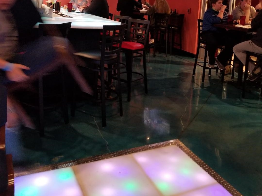 """Asia Cafe features televisions located throughout the restaurant and a state-of-the-art dance floor (seen in the foreground) called """"The Brain"""", developed by a neuroscientist specifically for the establishment."""