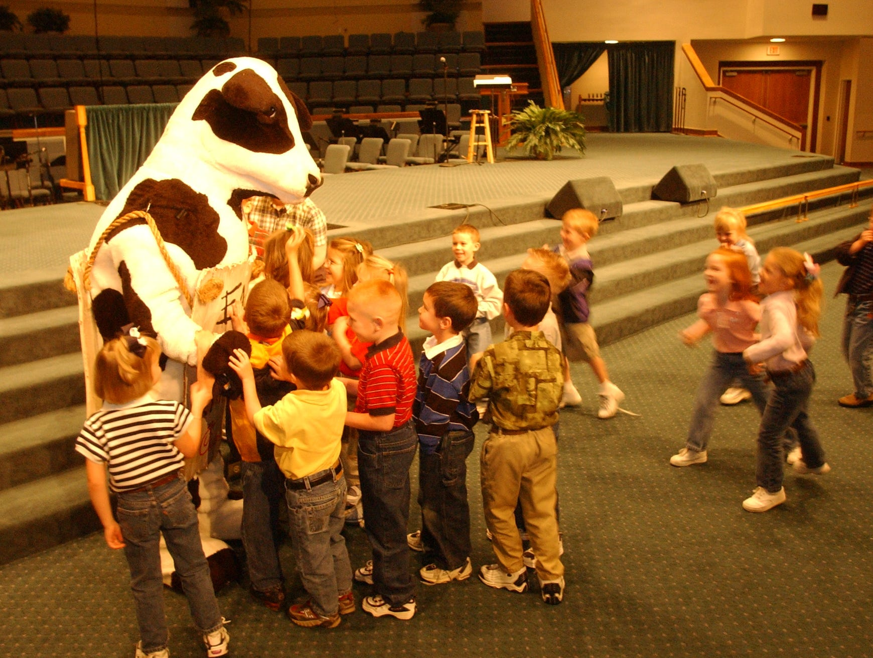 Children in Rebeckah Phelps kindergarden class at Grace Baptist Church School rush to hug the Chik-fil-A cow at the end of a Chapoel service in the Church Sanctuary.  Local Chick-fil-A restaurants including the Crown Point Plaza restaurant on Clinton Hwy. partner with elementary schools to promote character education through core essentials programs.  2003.