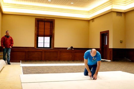 Greg Pinkstock installs carpet in the Fairfield County Commissioners' hearing room Monday, Jan. 7, 2019, in Lancaster. The room is undergoing a light renovation with newly painted walls and carpet among the projects.