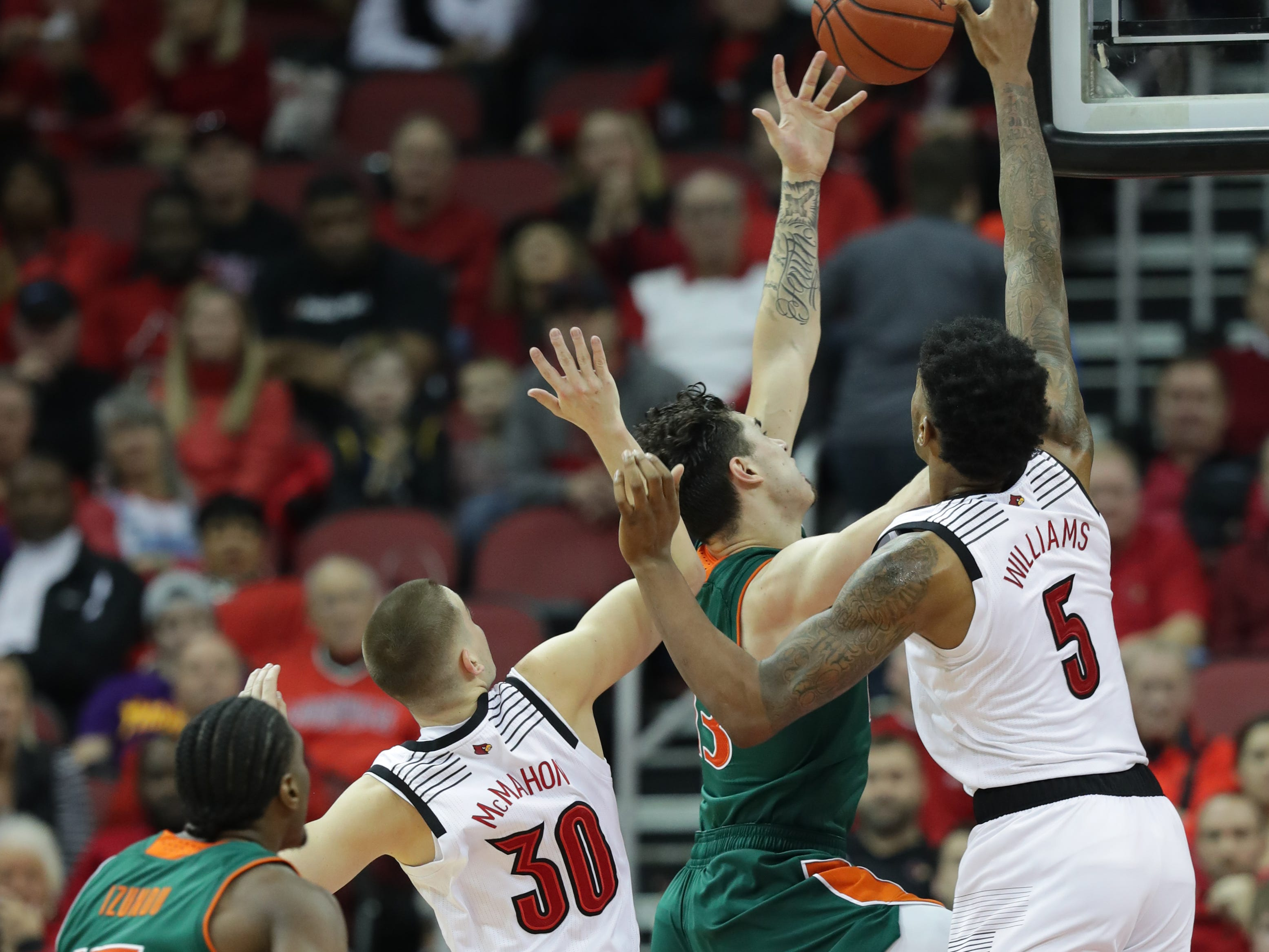 Miami's Anthony Mack drives to the basket against Louisville's Ryan McMahon and Malik Williams. Jan. 6, 2019.