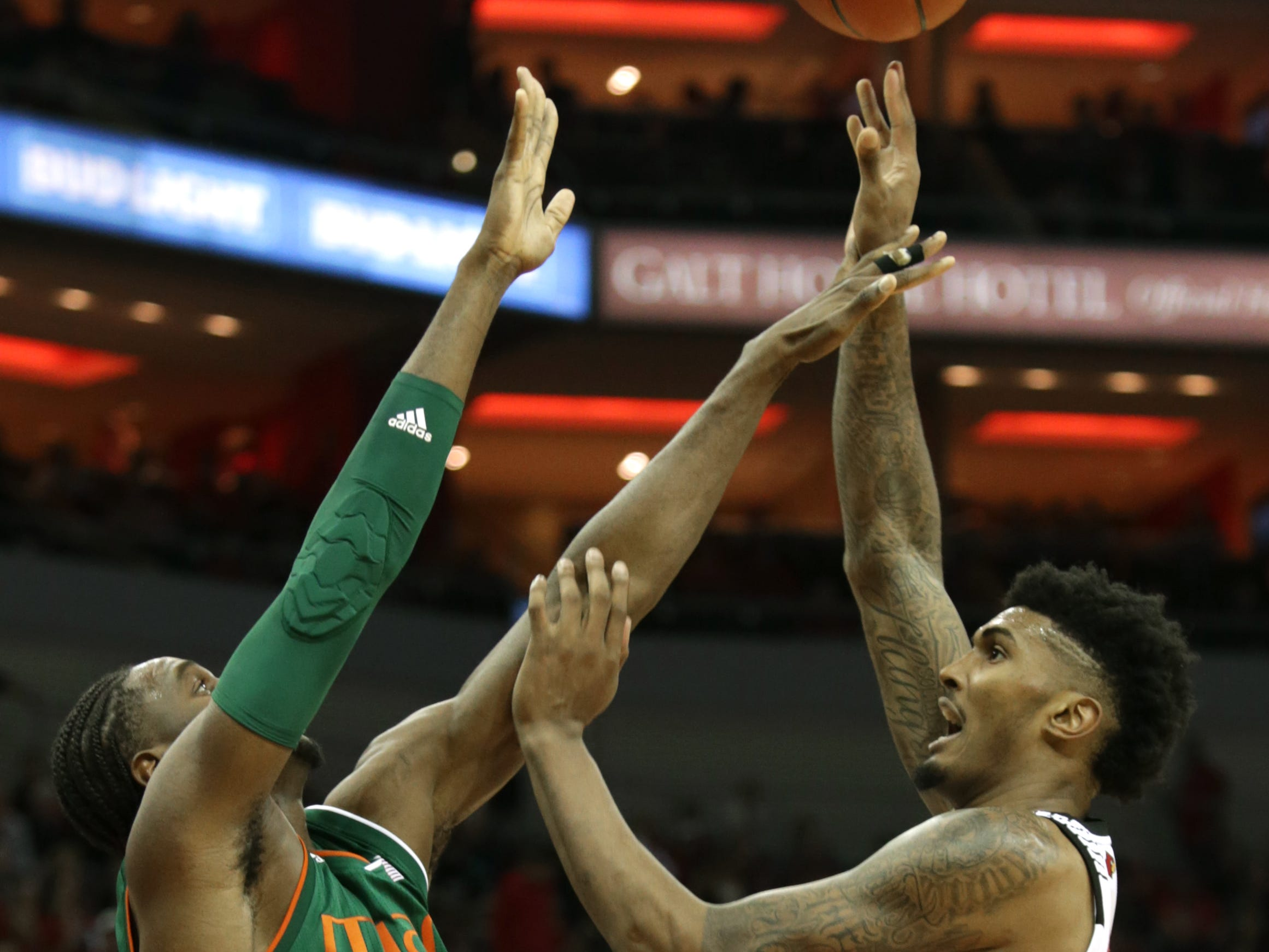 Louisville's Malik Williams gets a shot off against Miami's Eduka Izaundu. Williams scored 19 points in the game. Jan. 6, 2019.