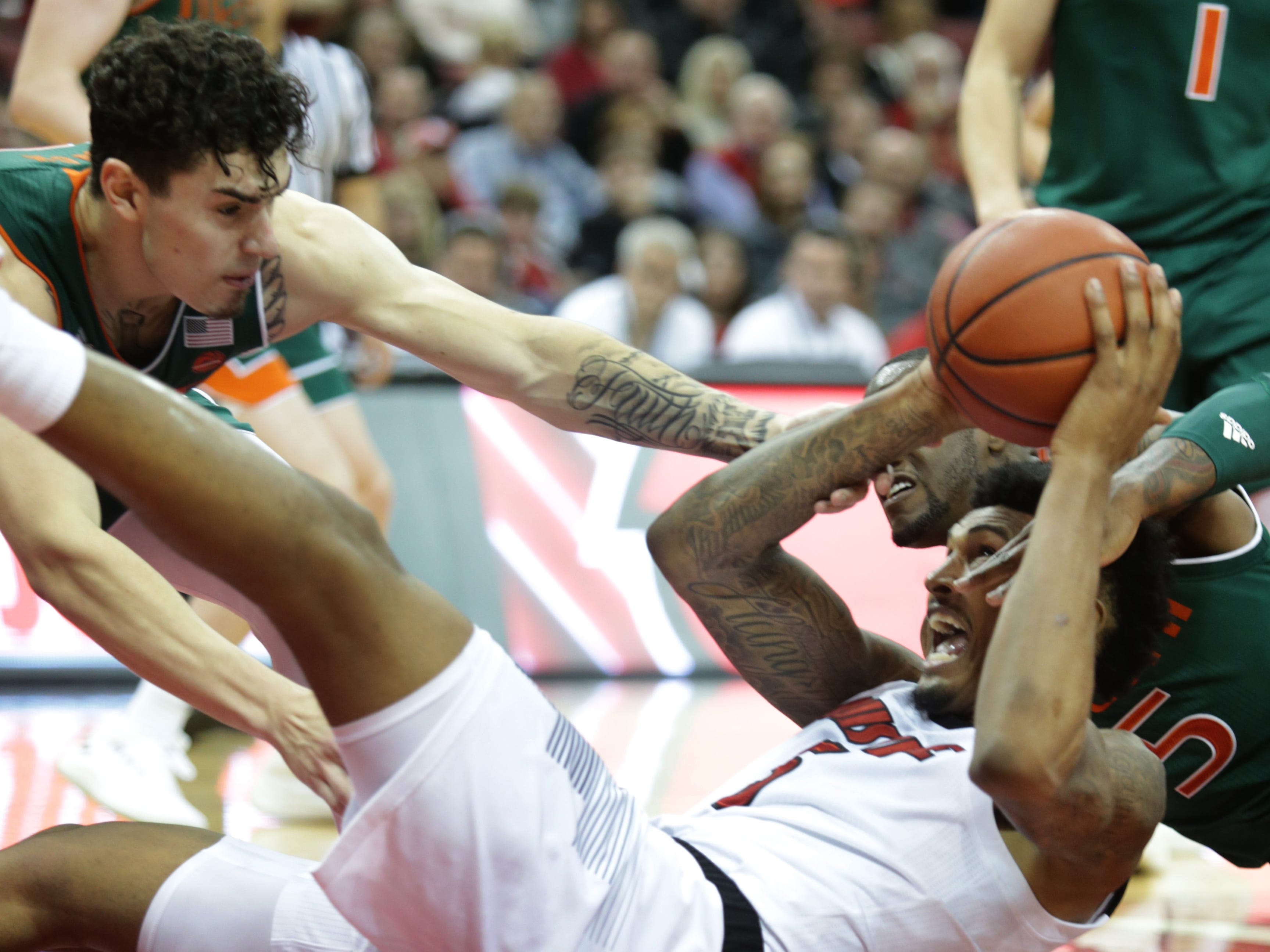 Louisville's Malik Williams right, battles for a loose ball against Miami's Anthony Mack, left. Jan. 6, 2019.