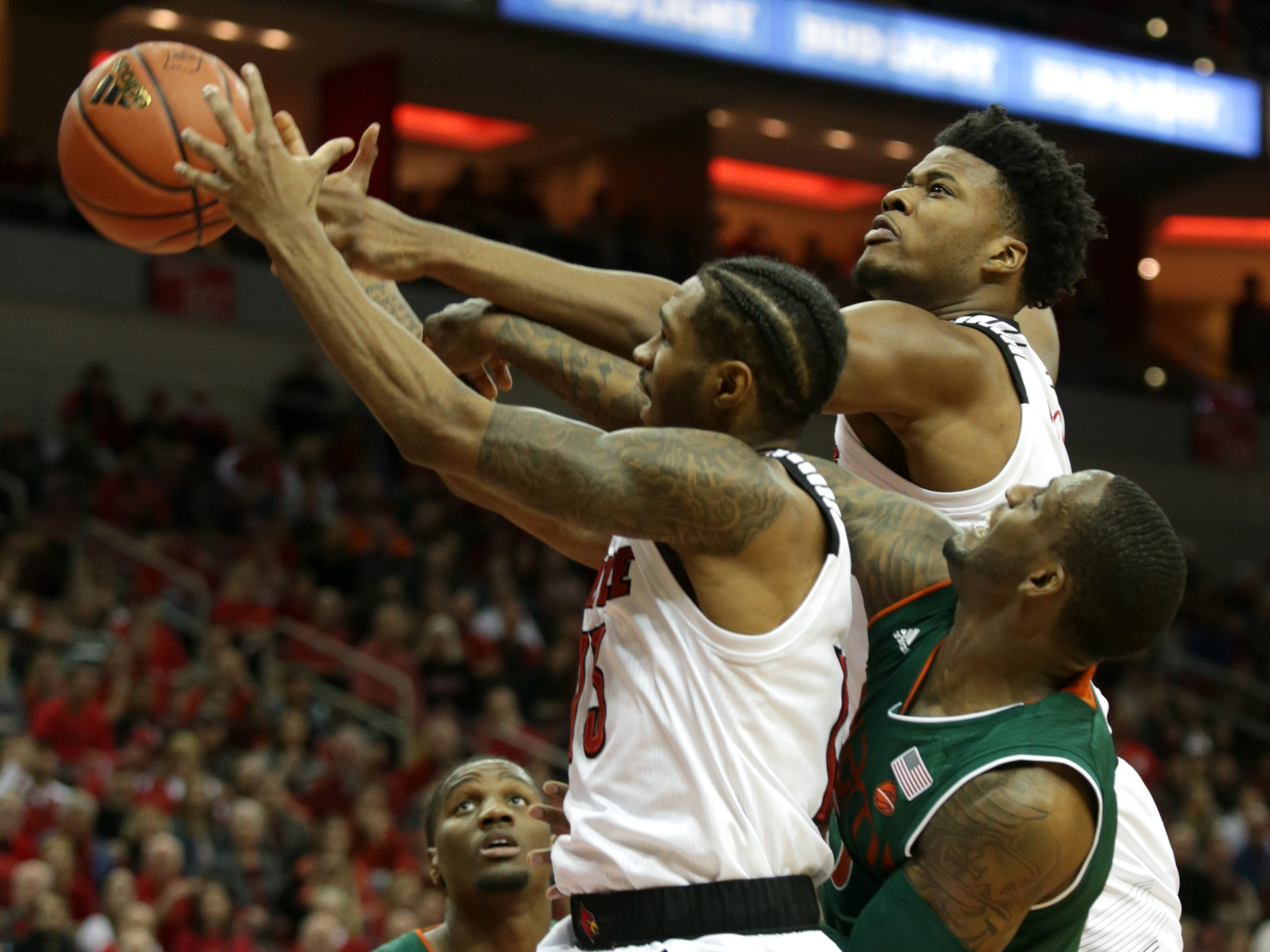 Louisville's V.J. King, left and Steven Enoch, top, battle for a round against Miami. Jan. 6, 2019.