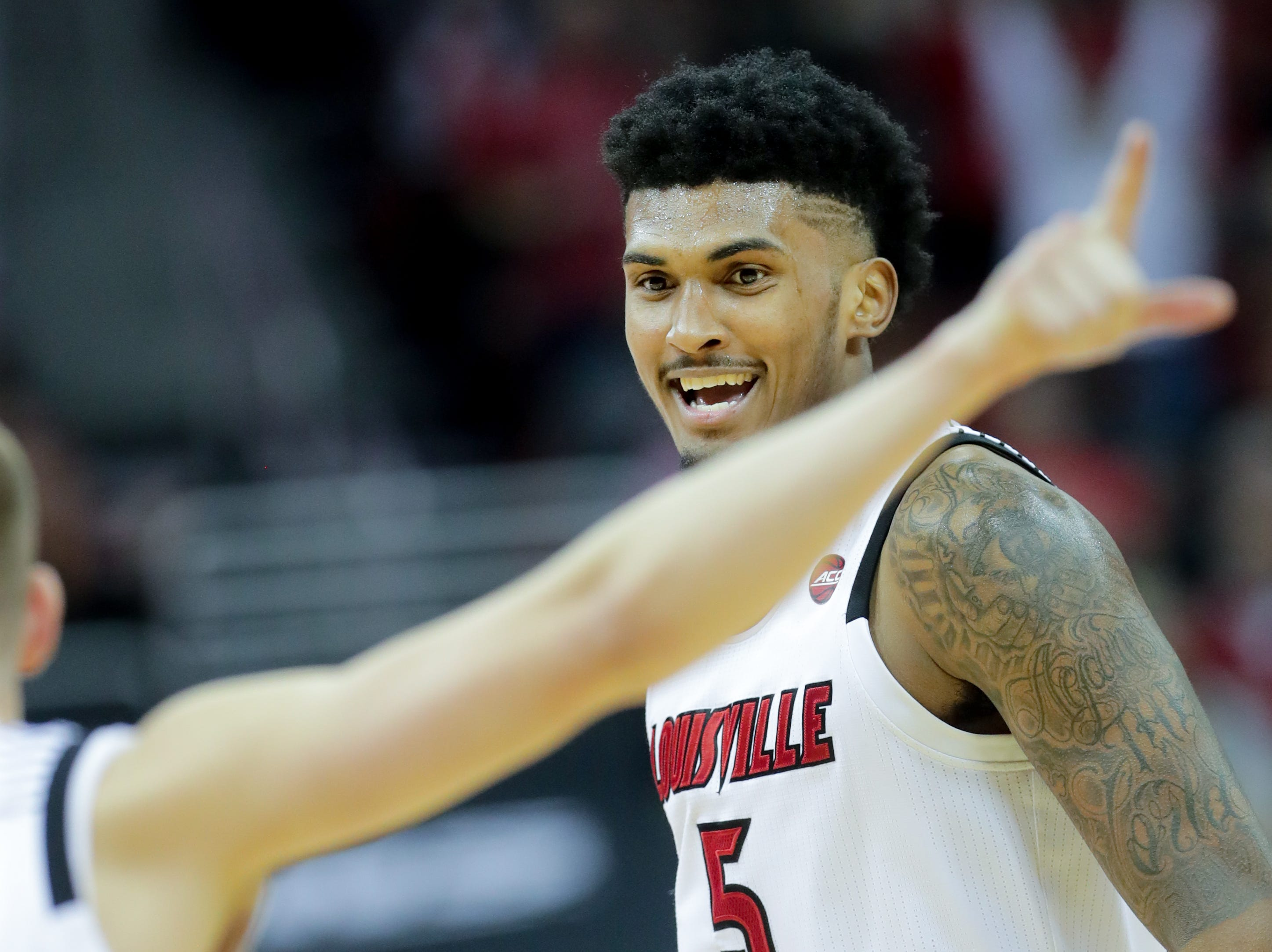 Louisville's Mailk Williams celebrates with teammate Ryan McMahon. Jan. 6, 2018