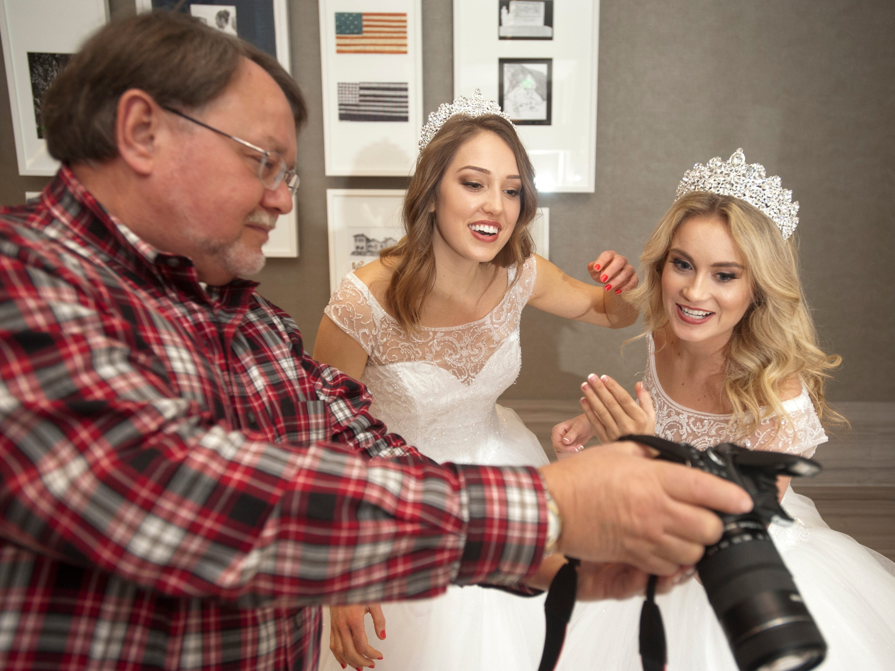 Elizabeth Seewer, center, and Allison Spears, right, look at a photo taken of them by Fillies President Debra Rayman's husband, Mitch.06 January 2019