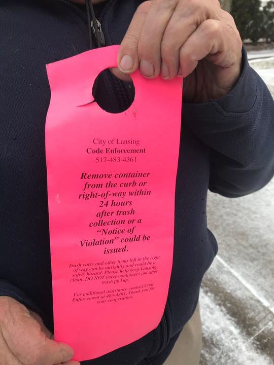 Charles Haynes, pictured Jan. 3, 2019, displays the warning he received about leaving garbage and recycling carts at the curb for more than 24 hours after emptying.