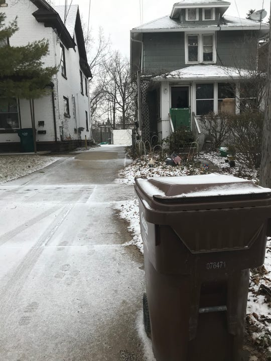 A garbage cart awaits pickup in front of Charles Haynes' home in the Green Oaks neighborhood. Lansing officials have warned Haynes and others about leaving the cart at the curb for more than 24 hours.