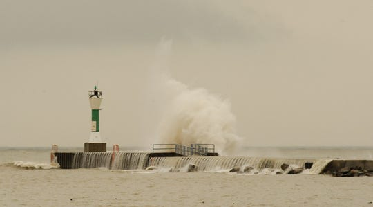 File - Waves on Lake Michigan crash into the south pier breakwater by the Manitowoc harbor Feb. 29, 2012. The tower in the photo is the South Pier Light Navigational Beacon that was washed away by strong waves on Lake Michigan Jan. 7.