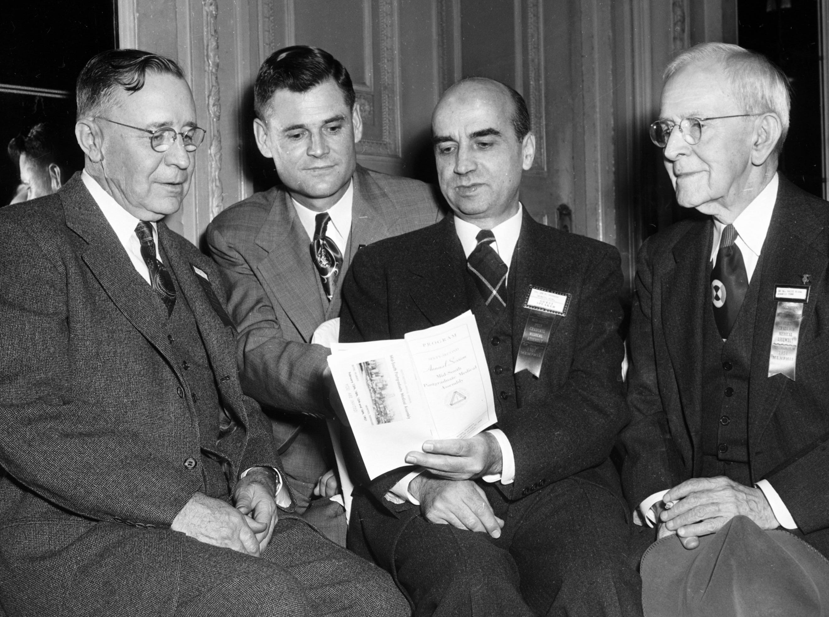 Dr. Ben E. Goodrich (Second Right) dealt with clinical problems related to high blood pressure within the lungs on 13 Feb 1951 in his talk before the Mid-South Post-Graduate Medical Assembly.  Discussing his paper with him are Dr. N.B. Ellis (Left) of Wilson, AR; Dr. W.H. Lunceford (Second Left) of Sardis, MS and Dr. William Britt Burns (Right) of Memphis.  Dr. Burns was vice president of the old Tri-State Medical Assembly in 1898, which preceded the present organization.  He maintains he hasn't missed a single meeting throughout the years.