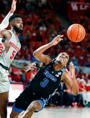 Memphis guard Jeremiah Martin loses control of the ball while driving the lane against Houston defender Corey Davis Jr. during the Tigers' loss Sunday.