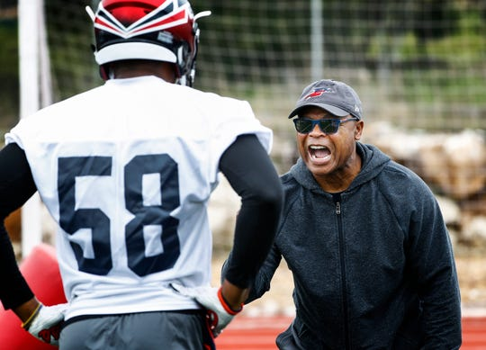 Memphis Express head coach Mike Singletary goes over drills with linebacker DeMarques Gates during morning practice at training camp in San Antonio.