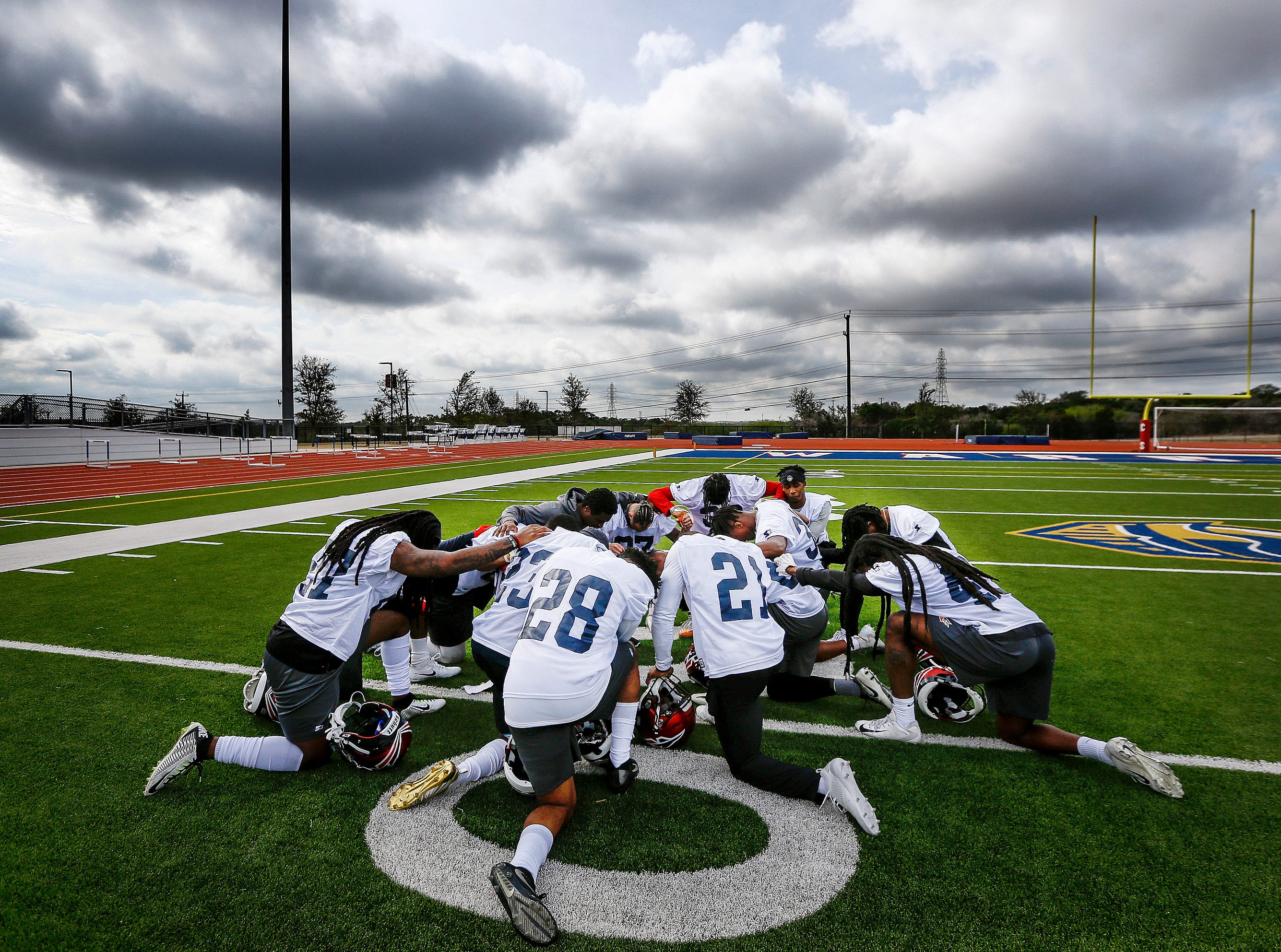 Under cloudy Texas skies, defensive teammates of the Memphis Express football team huddle up for a prayer after morning practice during training camp. Players with the eight teams of the Alliance of American Football league are in San Antonio for a month-long training camp. The Express will play their first game Sunday, Feb. 10th in Birmingham.