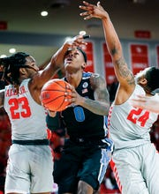 Memphis forward Kyvon Davenport (middle) is fouled while driving to the basket against Houston defenders Cedrick Alley Jr. (left) and Breaon Brady on Sunday.