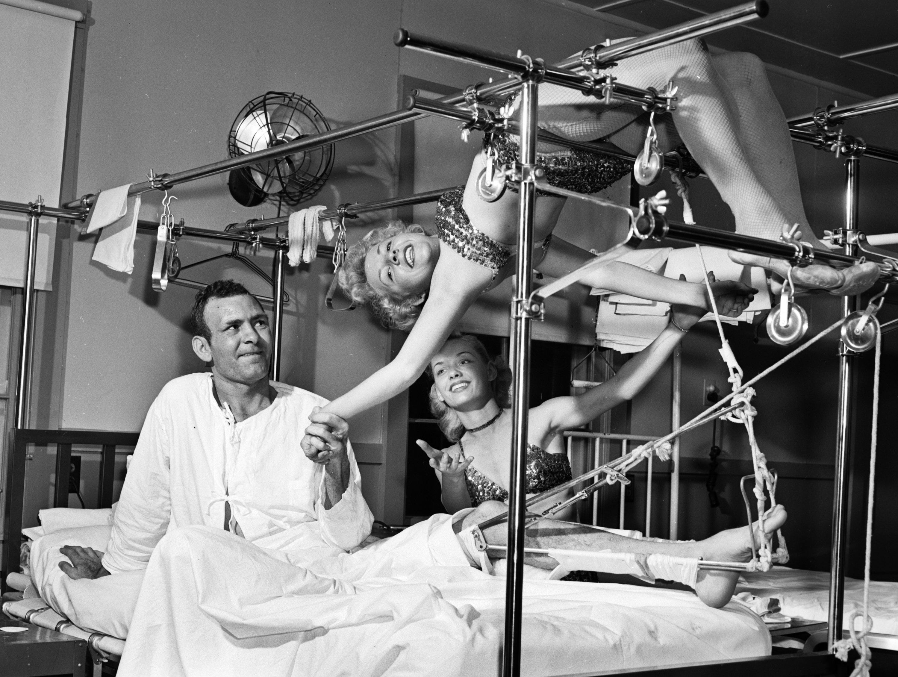 The Shrine Circus went to Memphis Naval Hospital at Millington in February 1951 for a special free performance and after the show went into the wards so even those in bed could see.  Army Sgt. Harvey Boles gives a happy helping hand to Pat McFarland when she goes into her acrobatic act on the bars over his bed.  Also giving support is Jo Power, another circus aerialist.