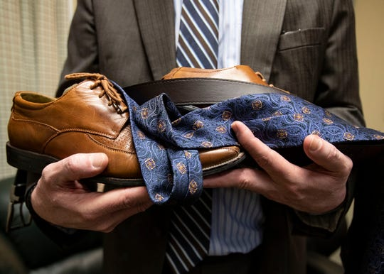 Gregg Carman, an attorney with the Shelby County Public Defender's office, holds shoes, a belt and tie which are used defendants when on trial.