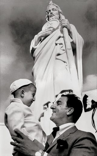 """A jubilant Danny Thomas hoists Bruce Frager up towards the statue of St. Jude Thaddeus in front of St. Jude Research Hospital at Jackson and Lauderdale at the formal opening of the hospital February 4, 1962. """"This is the greatest day of my life,"""" the television performer observed. """"If I should die this minute, I would know why I was born."""" Some 9,000 people turned out for the opening."""