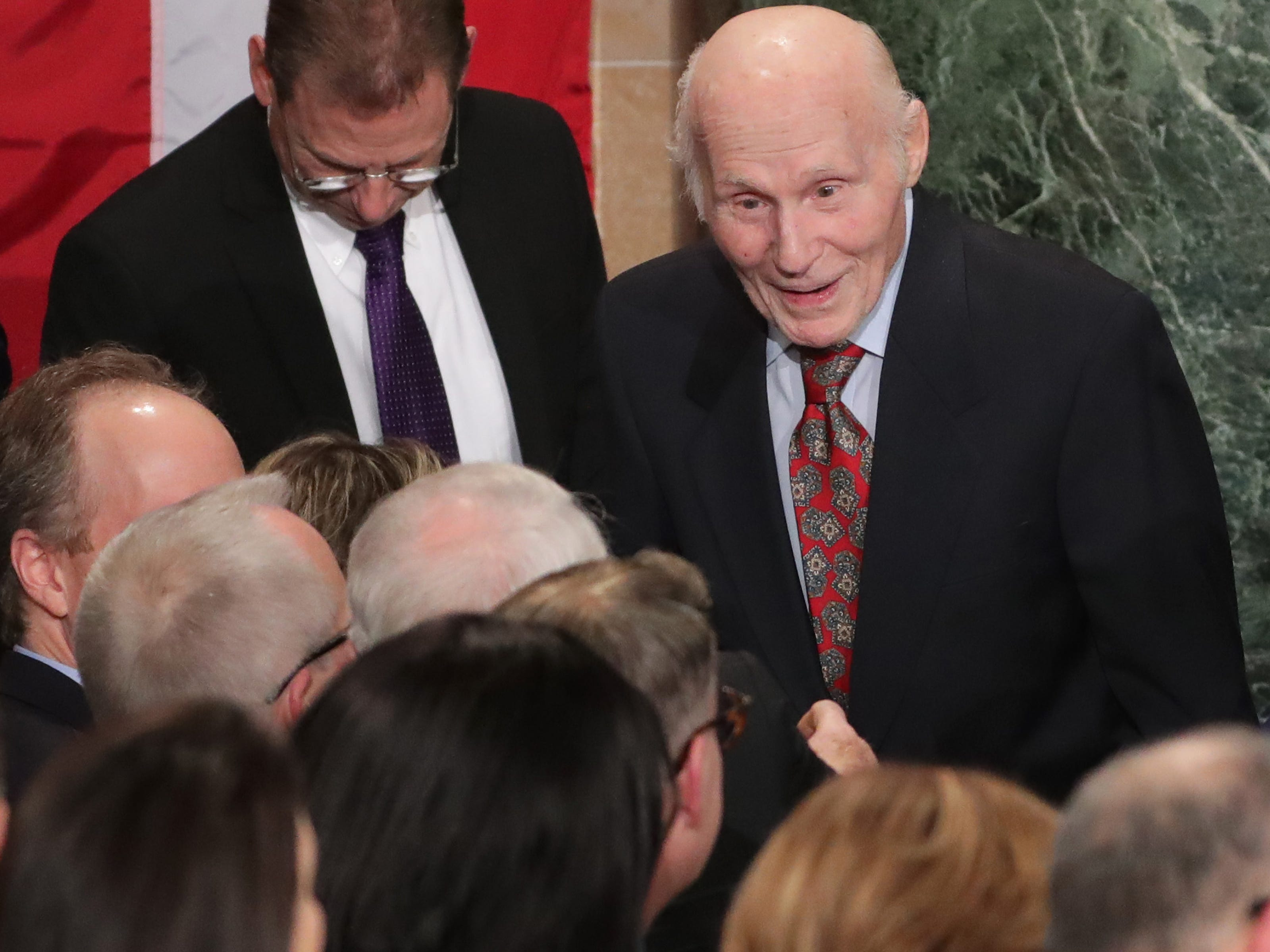 Former U.S. Sen. Herb Kohl finds his seat before the inauguration.