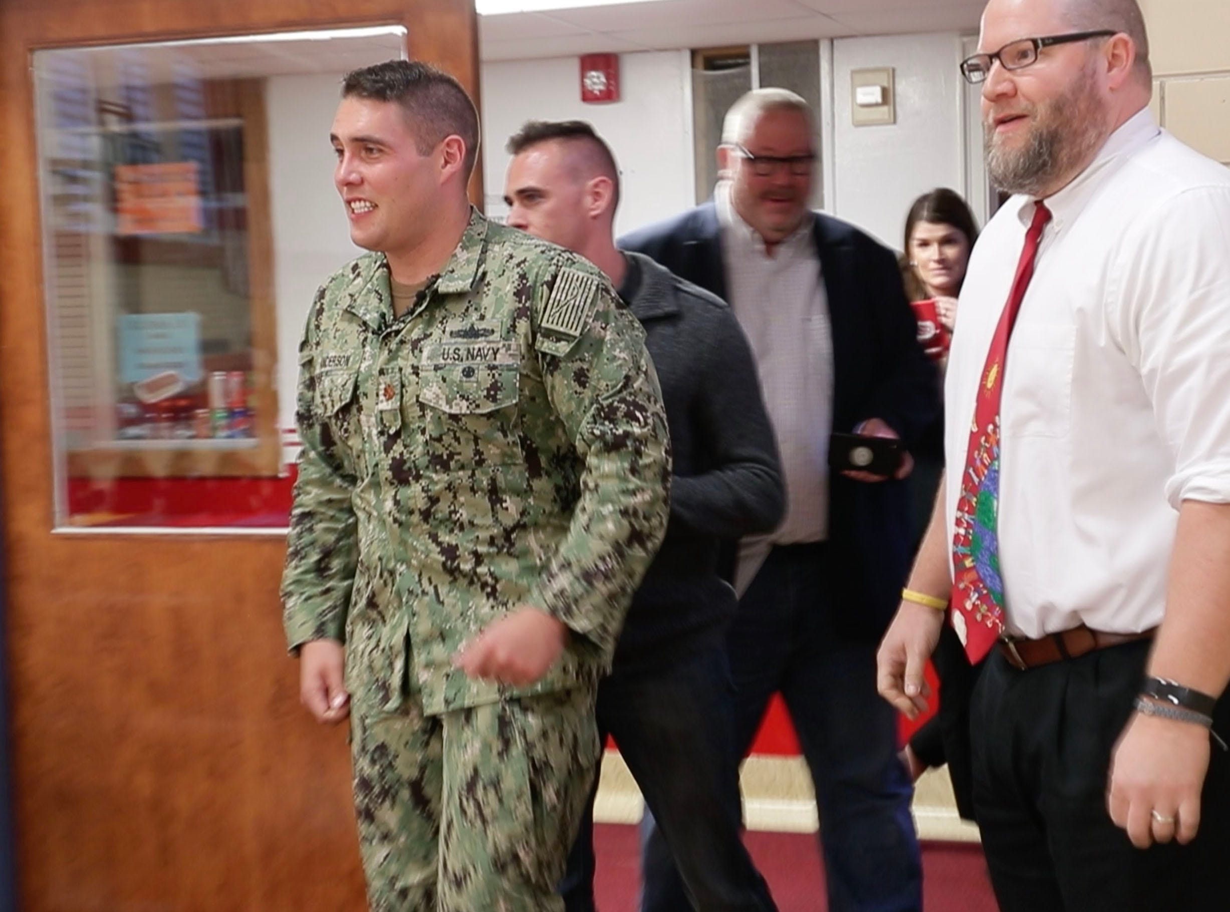 Navy Lt. Cmdr. Jon-Andrew Anderson-Ingebrigtsen enters the gym after he returned from a 20-month deployment and surprised his 7-year-old son, Ethan Anderson, a second- grader at St. Monica Catholic School in Whitefish Bay on Monday.