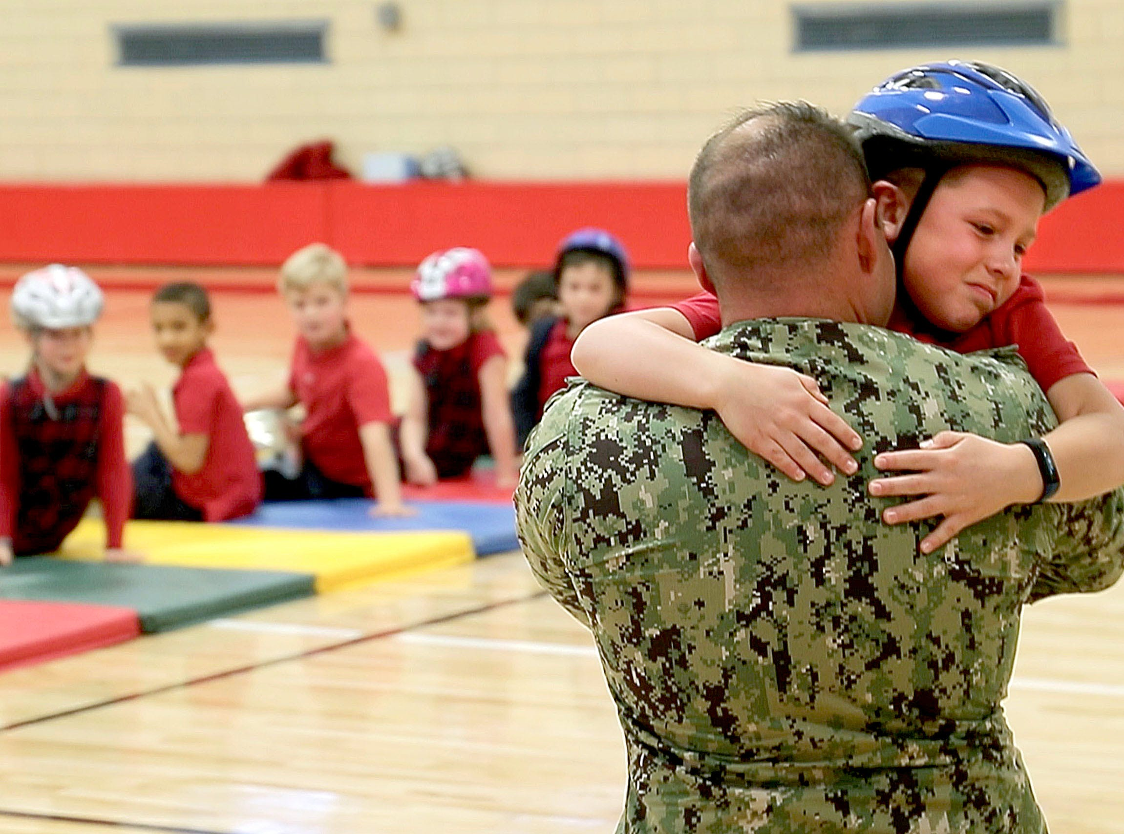 Ethan Anderson hugs his father, Navy Lt. Cmdr. Jon-Andrew Anderson-Ingebrigtsen, after he returned from a 20-month deployment and surprised his 7-year-old son.
