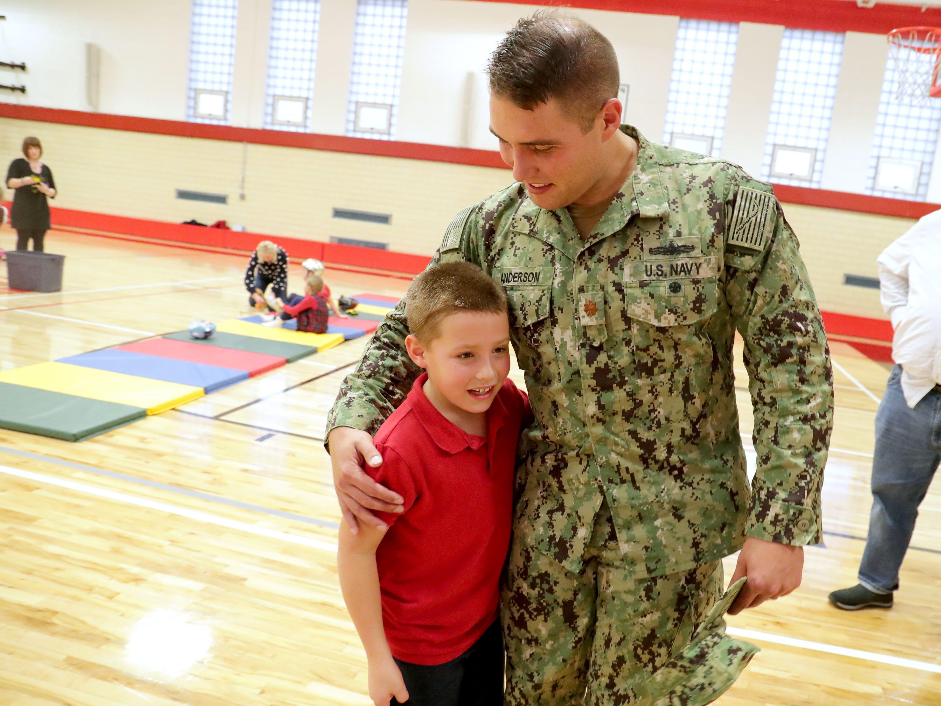 Ethan Anderson hugs his father, Navy Lt. Cmdr. Jon-Andrew Anderson-Ingebrigtsen.