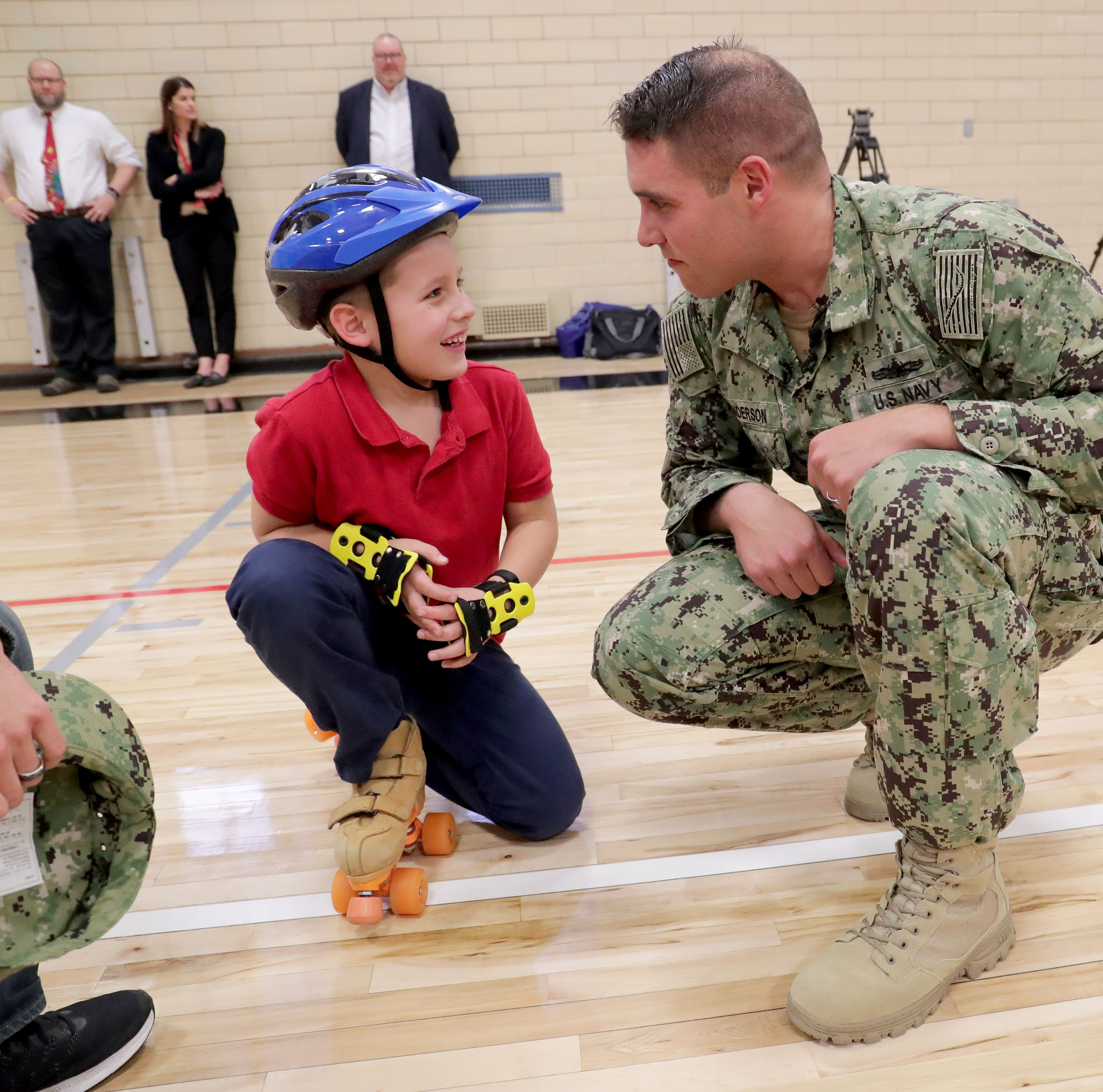 Apart for almost two years, Navy dad surprises 7-year-old son during gym class
