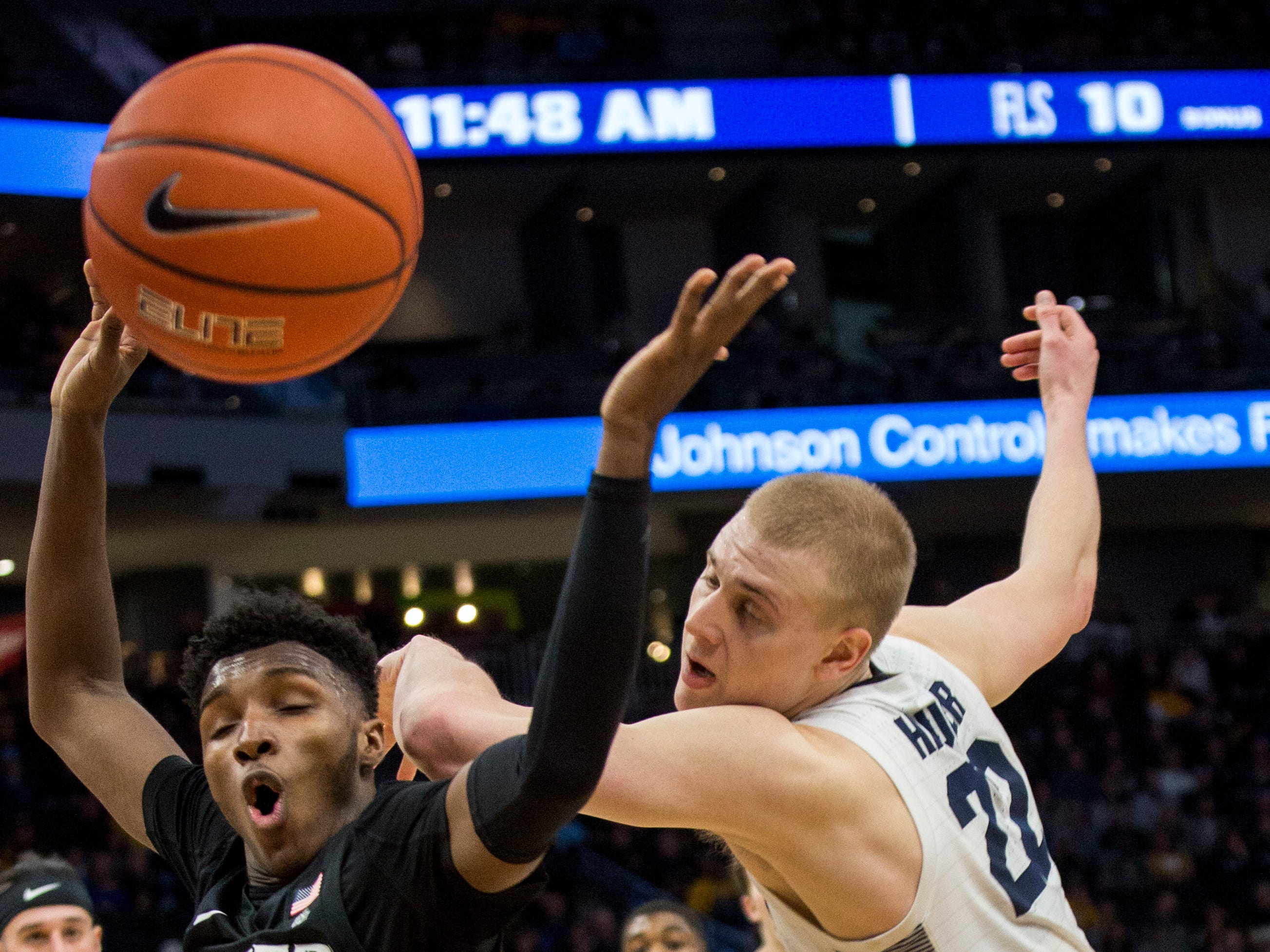 Marquette forward Joey Hauser and Xavier guard Keonte Kennedy battle for a loose ball on Sunday.