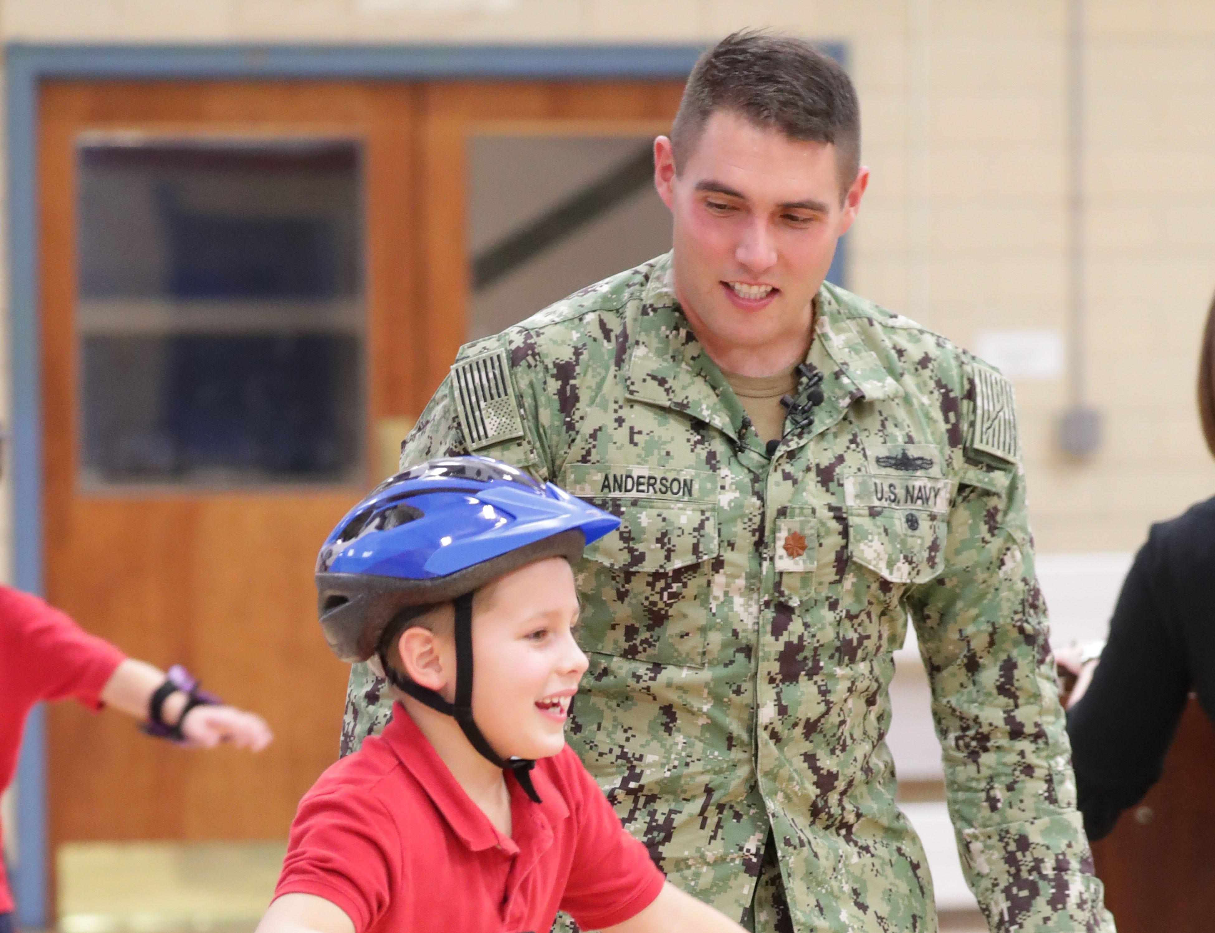 Navy Lt. Cmdr. Jon-Andrew Anderson-Ingebrigtsen helps his son on skates in gym class.