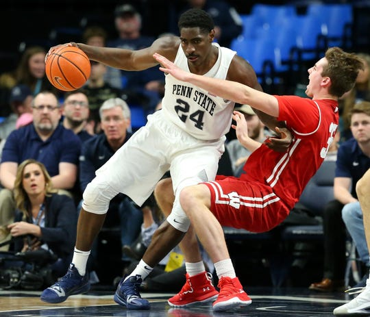Wisconsin forward Nate Reuvers draws a charging foul on Penn State forward Mike Watkins early in the second half on Sunday.