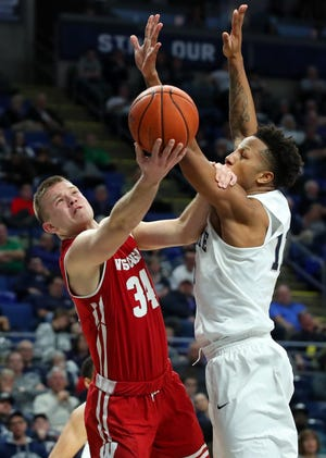 The Badgers' Brad Davison puts up a shot under the arms of Penn State forward Lamar Stevens during the second half Sunday. UW's sophomore guard finished with 14 points and seven rebounds against the Nittany Lions.