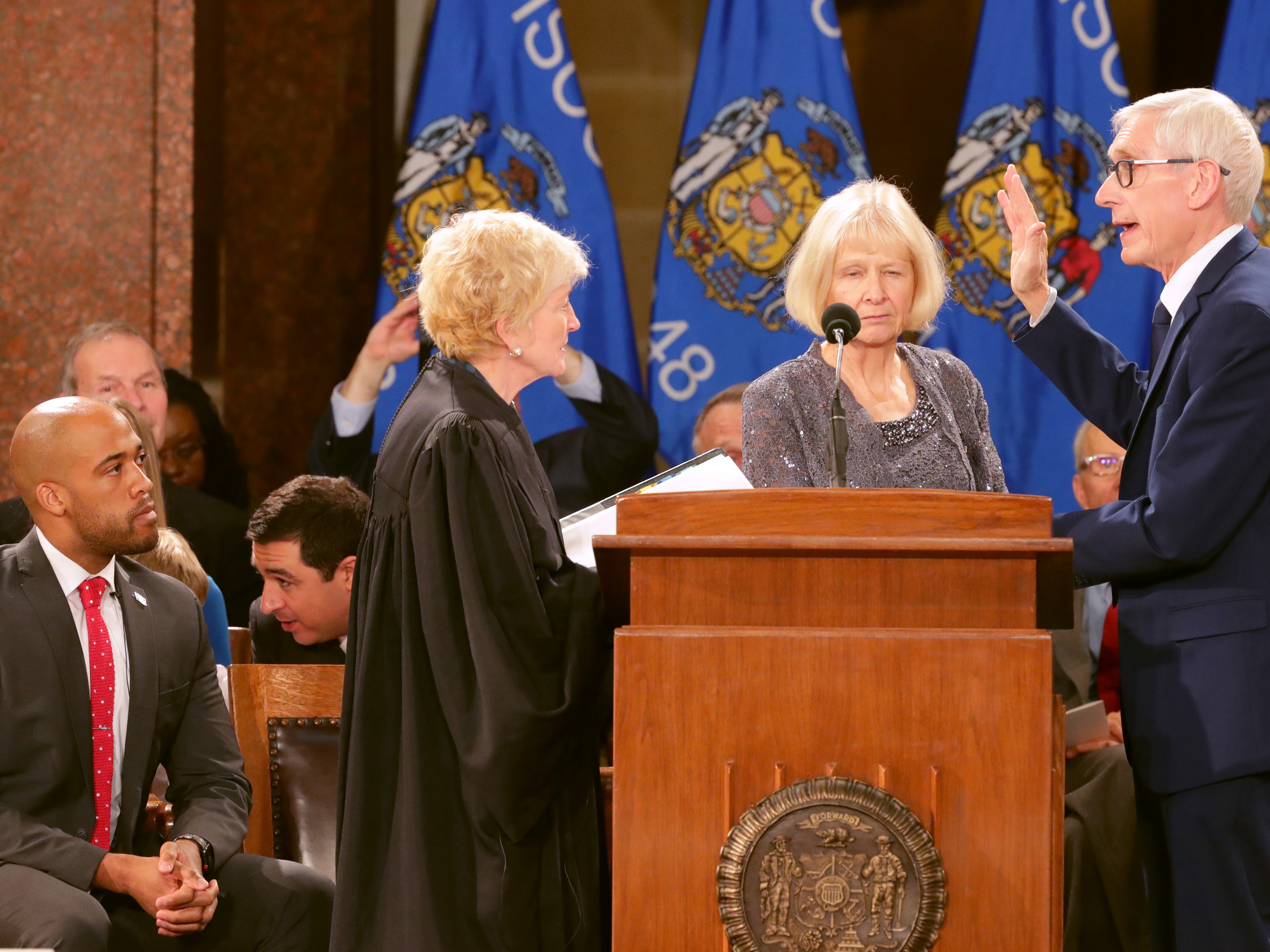 Tony Evers (right) is sworn in as governor by Wisconsin Supreme Court Chief Justice Patience D. Roggensack during the inauguration for the state's constitutional officers at the Capitol in Madison, Wis. Looking on is Evers' wife, Kathy (center), and Lt. Gov. Mandela Barnes (left).