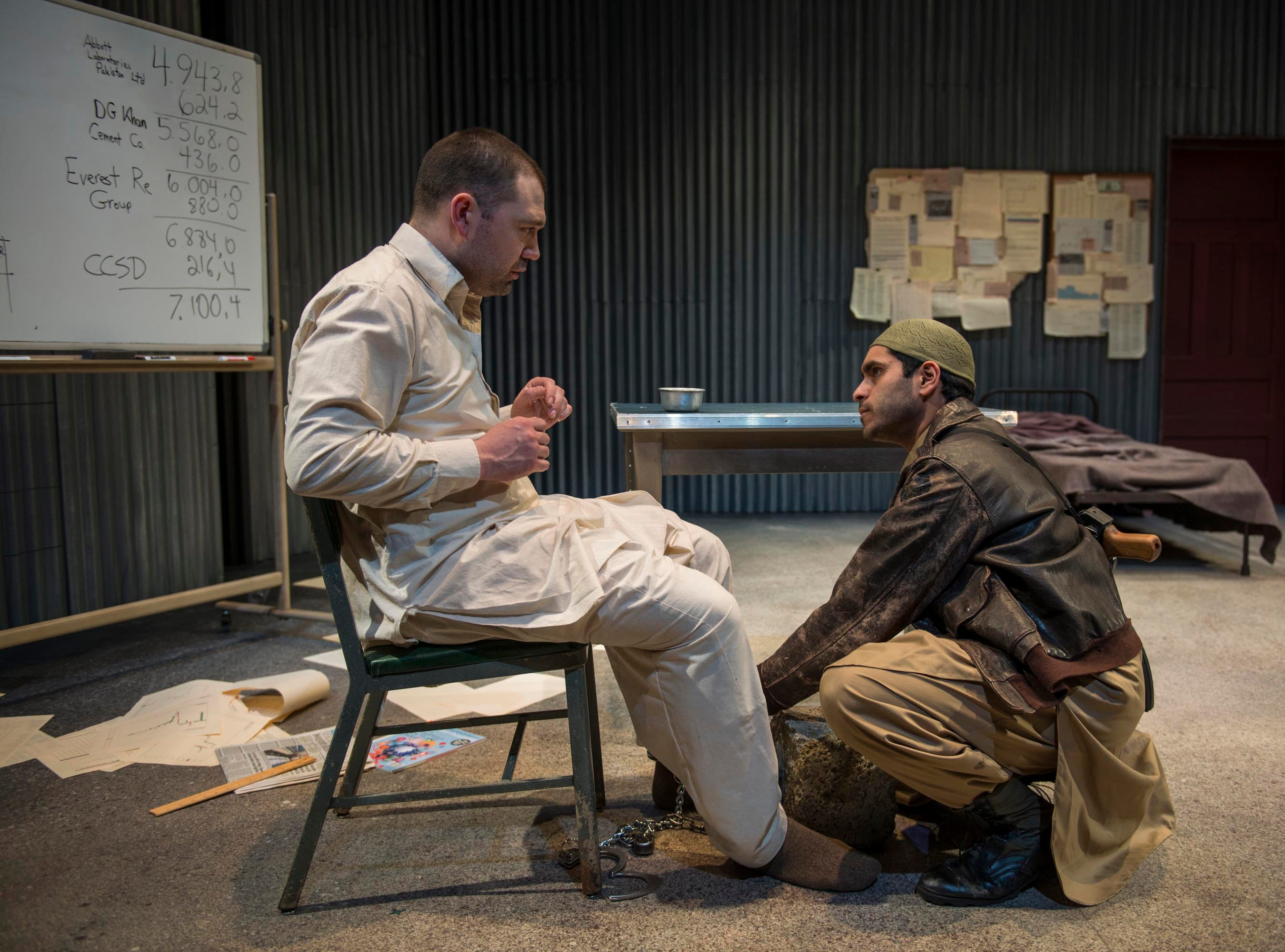 "Owais Ahmed (right) tends to Tom Coiner in the Milwaukee Repertory Theater's production of Ayad Akhtar's ""The Invisible Hand."" Akhtar is a Brookfield Central High School alum."