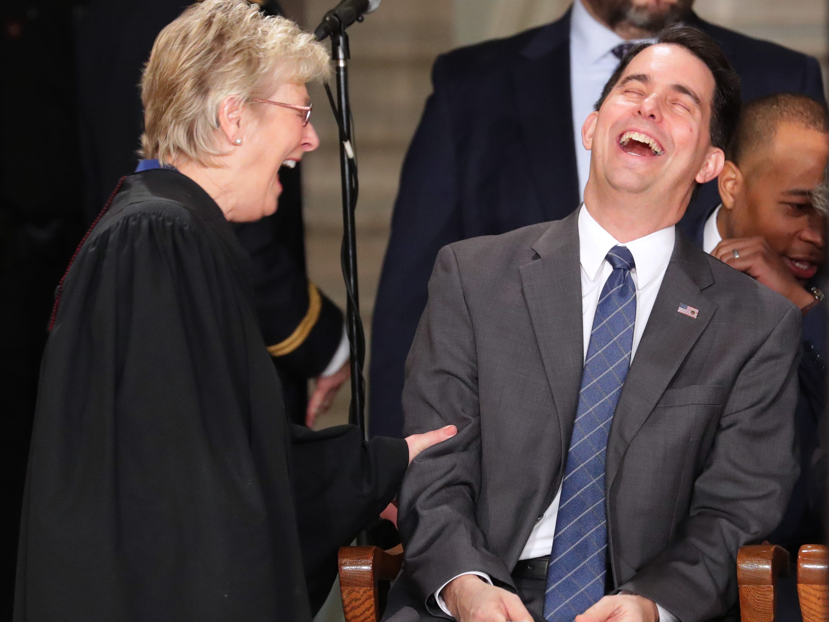 Associate Justice of the Wisconsin Supreme Court Ann Walsh Bradley (left) jokes with outgoing Gov. Scott Walker  before the inaugural event.