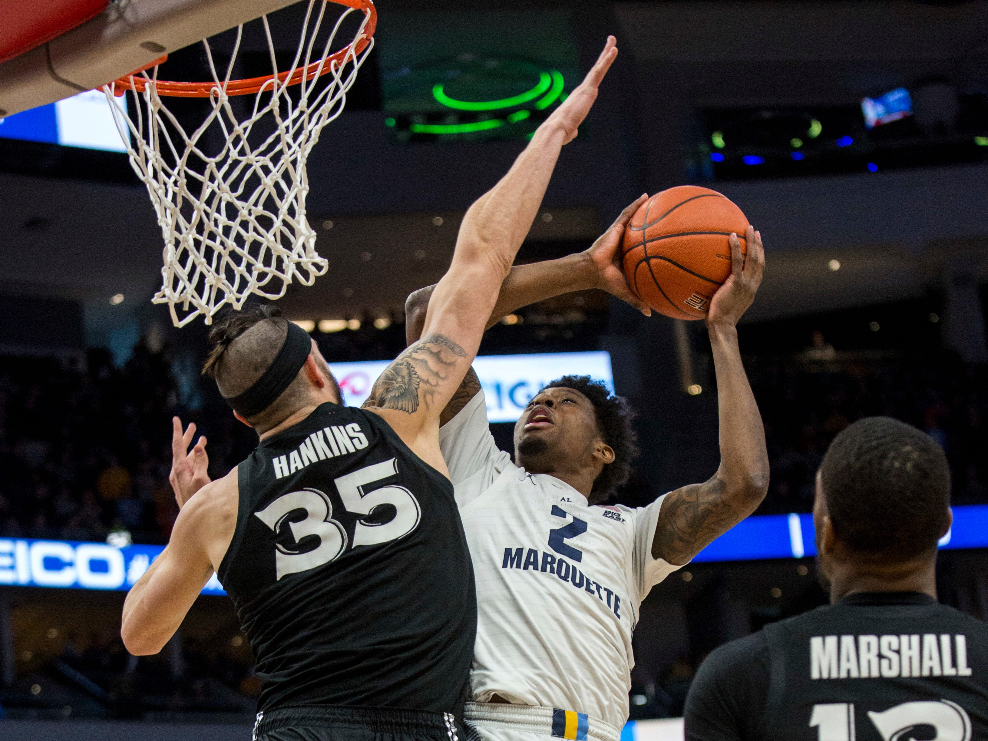 Marquette forward Sacar Anim puts up a shot down low that's contested by Xavier forward Zach Hankins during the first half Sunday.