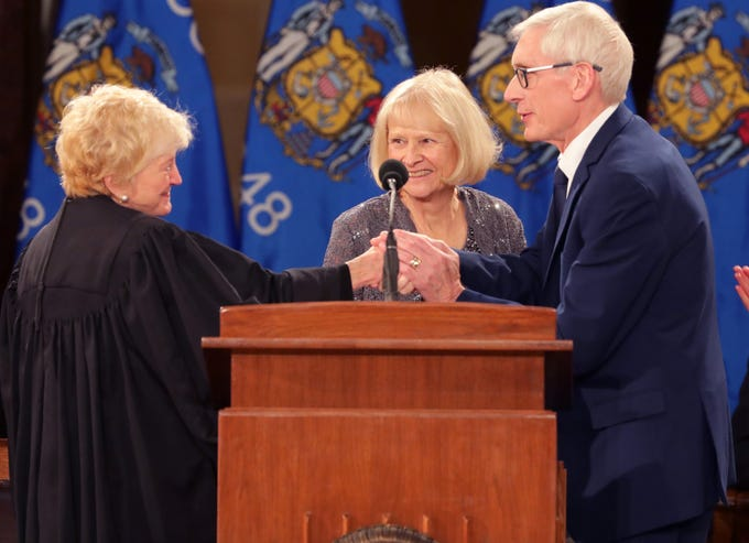 Tony Evers (right) is sworn in as governor by Wisconsin Supreme Court  Chief Justice Patience D. Roggensack (left) during the inauguration for the state's constitutional officers at the Capitol in Madison, Wis. Looking on is Evers' wife, Kathy.