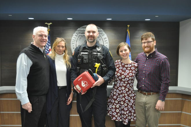Seconds after having a heart attack, Tim Kerwin (left) received CPR from Joel and Jessica Feih (right). Also pictured are Tim's wife Michele Kerwin and Whitefish Bay Police Officer Derek Bonkoski.