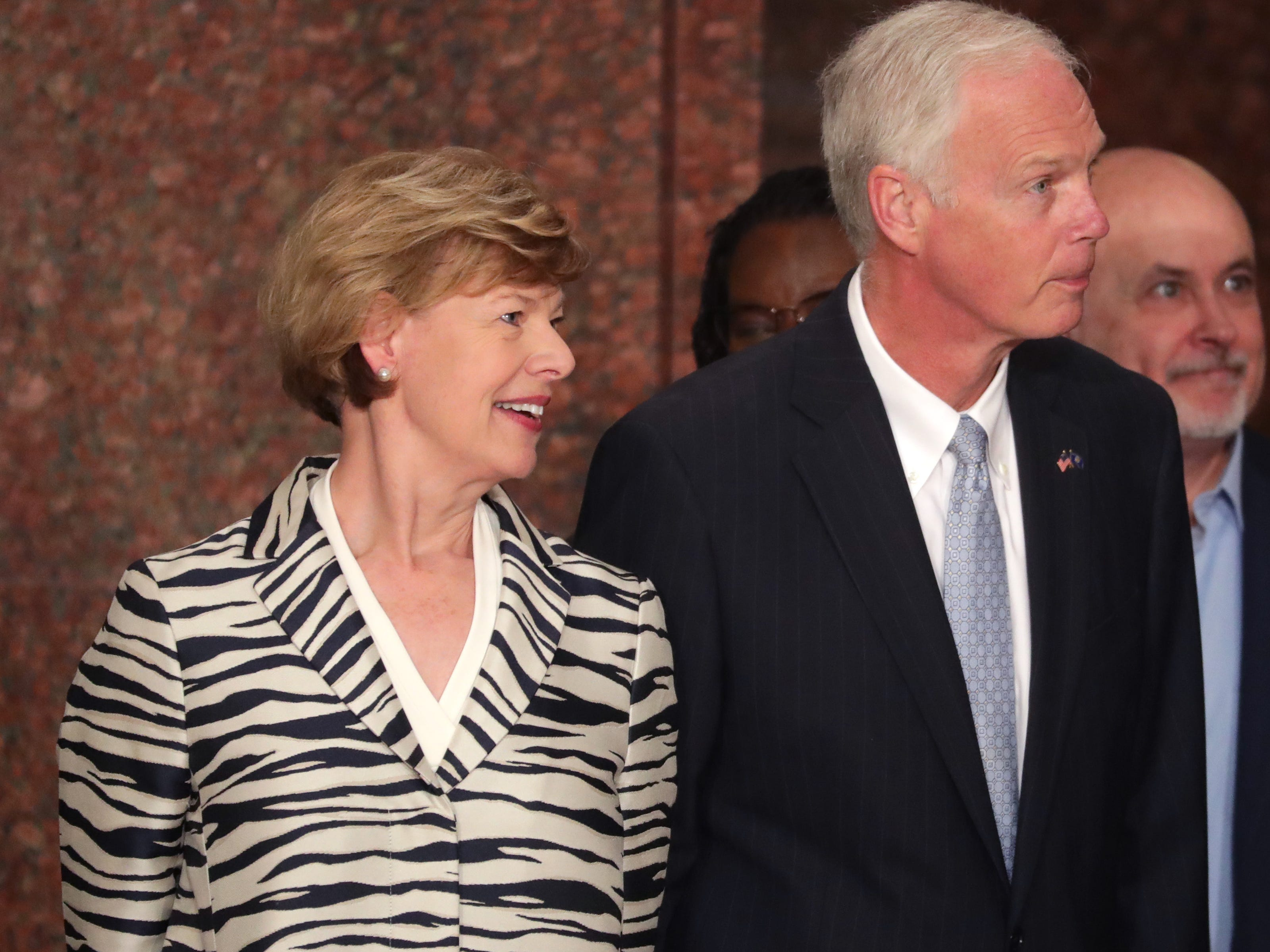 U.S. Sens. Tammy Baldwin (left) and Ron Johnson take their seats before the ceremony.