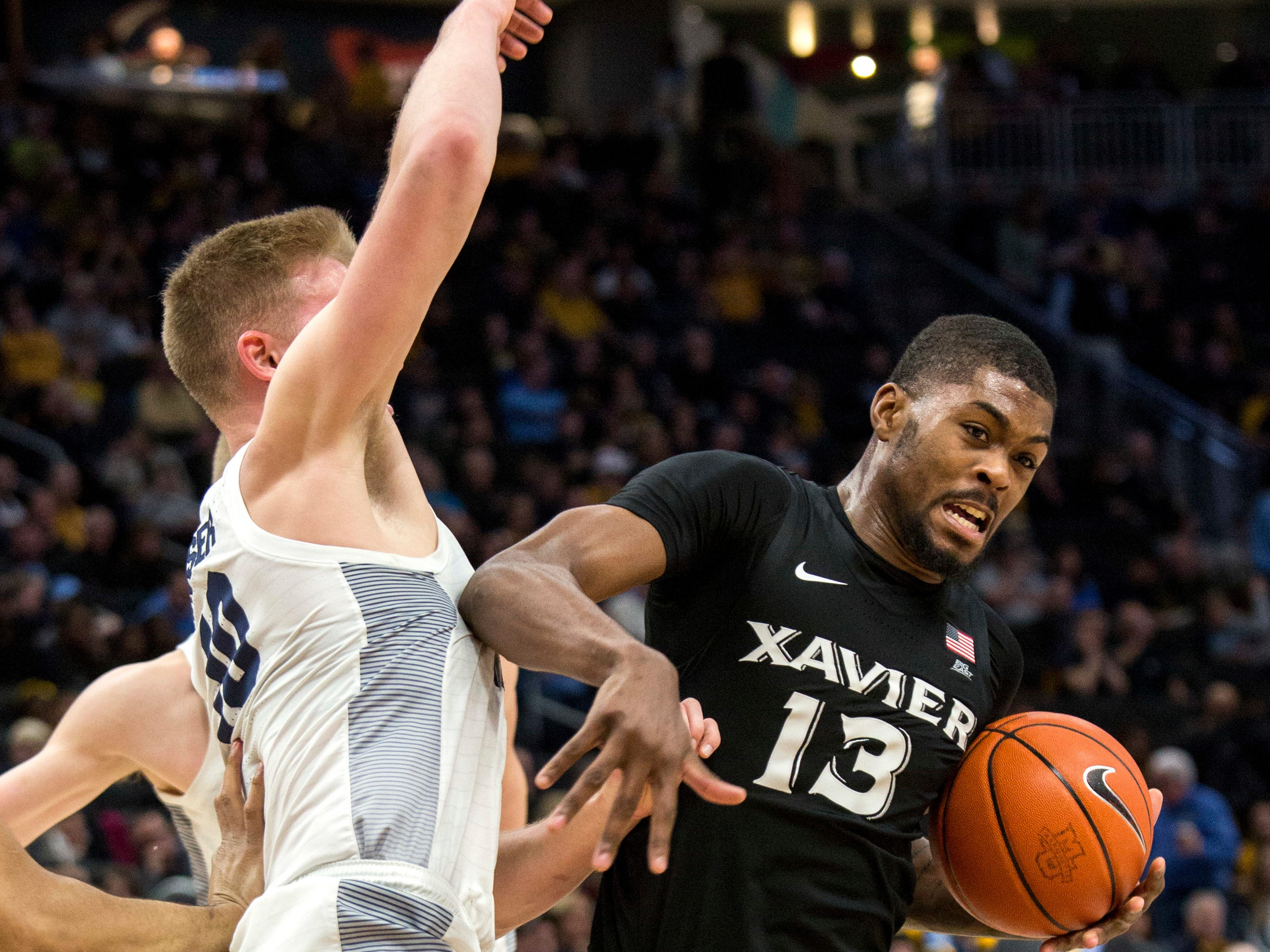 Xavier forward Naji Marshall works down low against Marquette forward Sam Hauser during the second half Sunday.