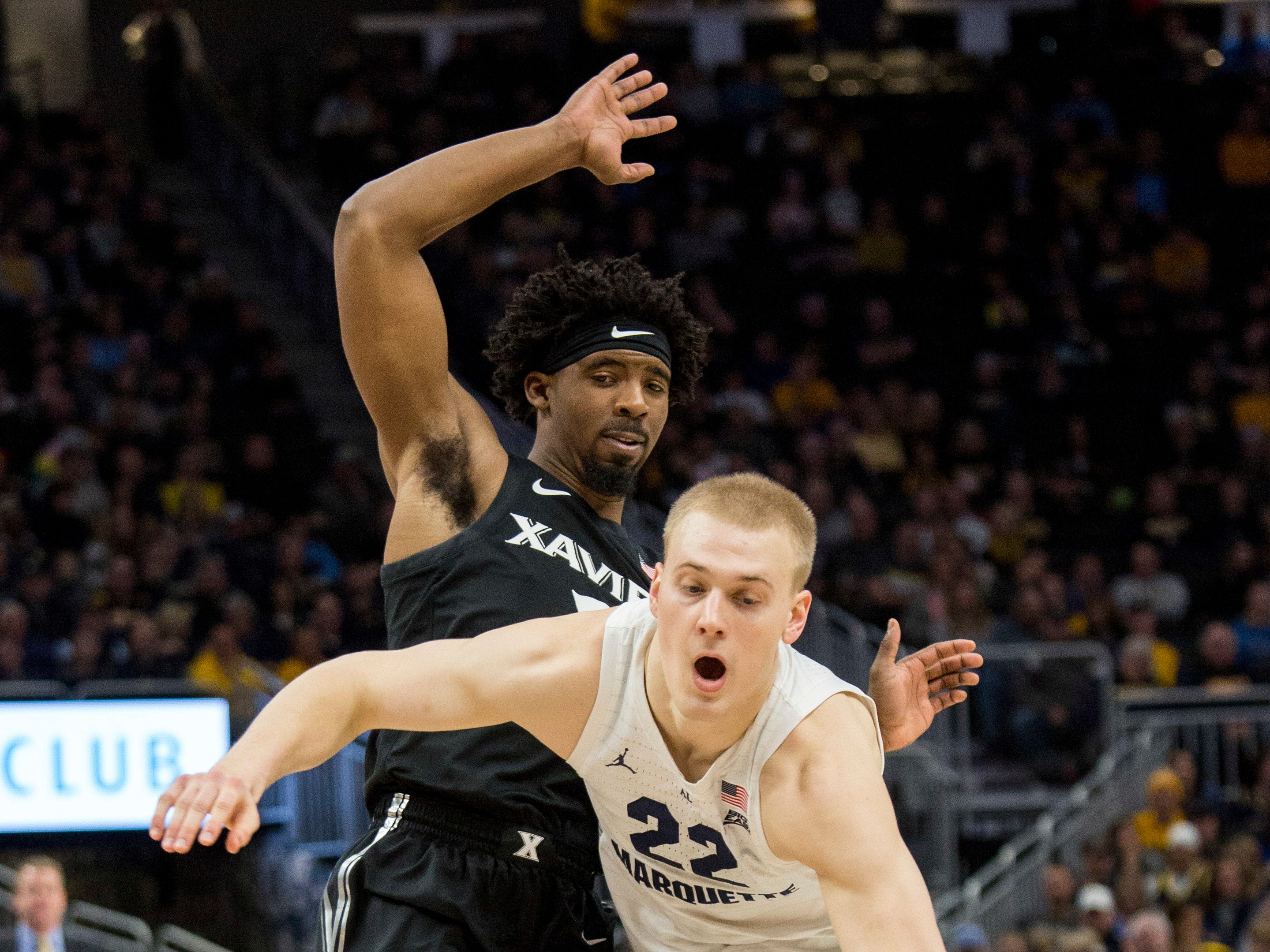 Marquette forward Joey Hauser drives past Quentin Goodin of Xavier during the first half Sunday afternoon at Fiserv Forum.