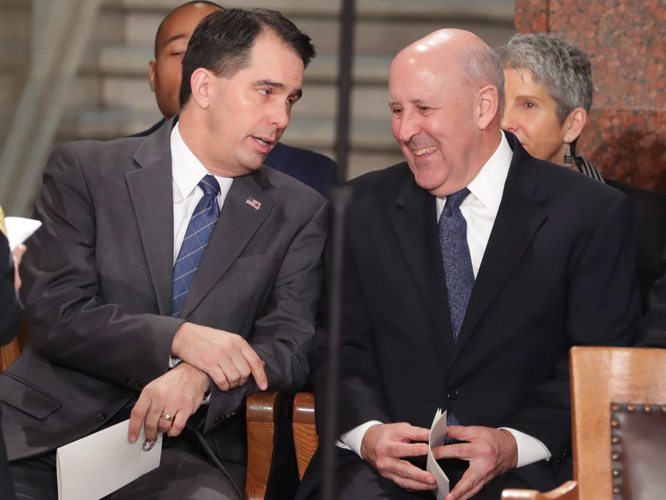 Outgoing Gov. Scott Walker (left) speaks to his predecessor,  Jim Doyle, during the inauguration.