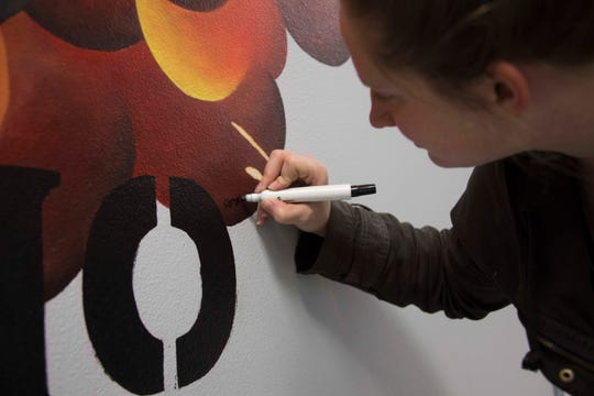 U.S. Air Force Staff Sgt. Ashley Johnson, 707th Maintenance Squadron munitions technician, signs a mural she completed for the 307th MXS at Barksdale Air Force Base, Louisiana, Jan. 4, 2019.