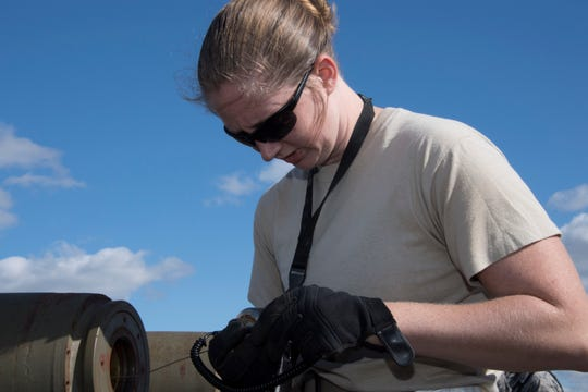 U.S. Air Force Staff Sgt. Ashley Johnson, a munitions technician assigned to the 707th Maintenance Squadron, performs maintenance on a munition during Ample Strike 18 at Royal Air Force Fairford, England, Sept. 7, 2018.   When not building munitions, Johnson can be found practicing her love of art.