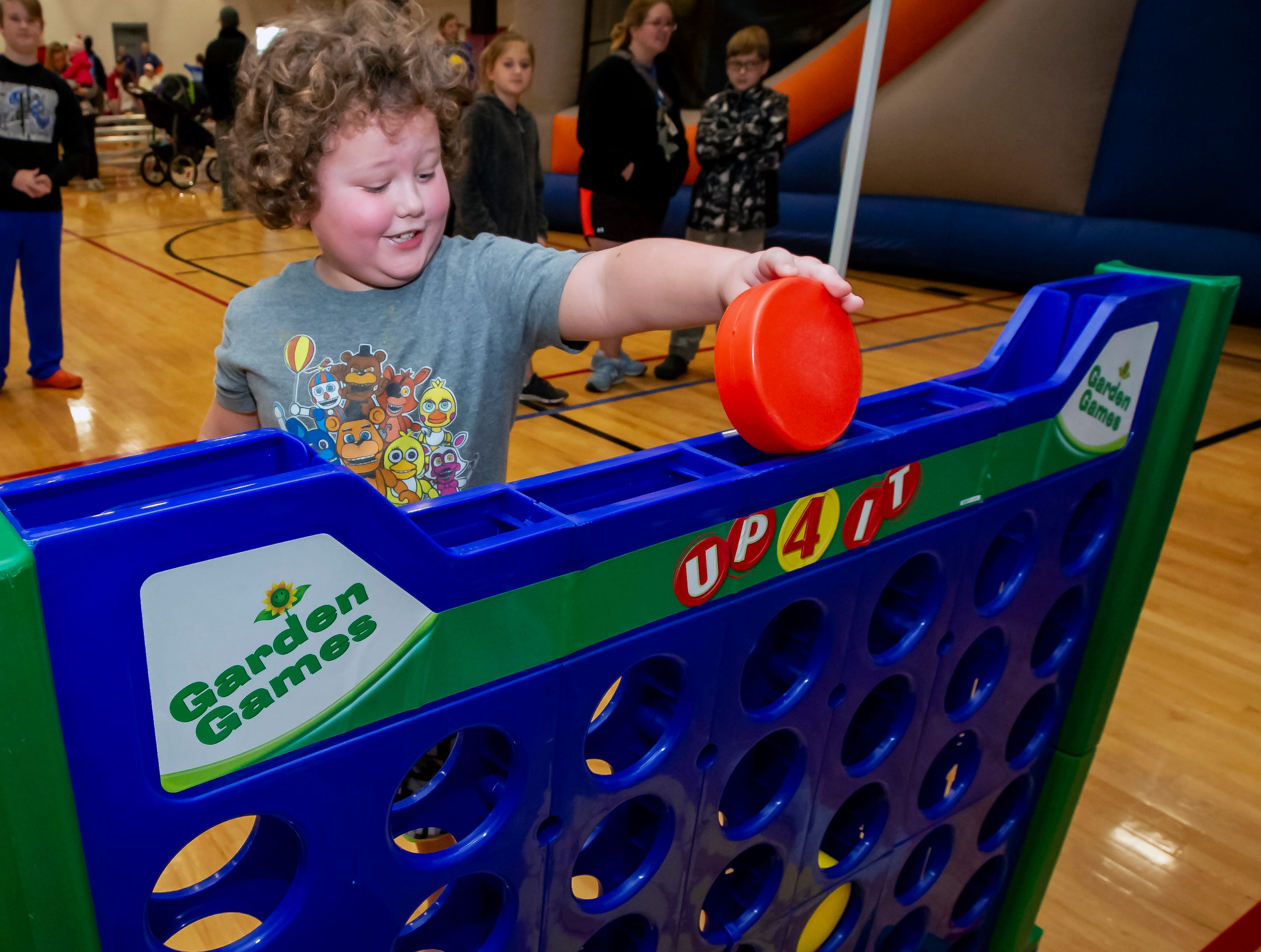 Rory Brock plays a carnival game at the 17th annual Polar Bear Plunge held at SportsCom on Saturday Jan. 5, 2019.
