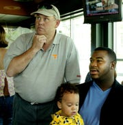 Albert Haynesworth (right) watches the 2002 NFL Draft with his then-11-month-old son, Ahsharri, and former Tennessee football coach Phillip Fulmer.